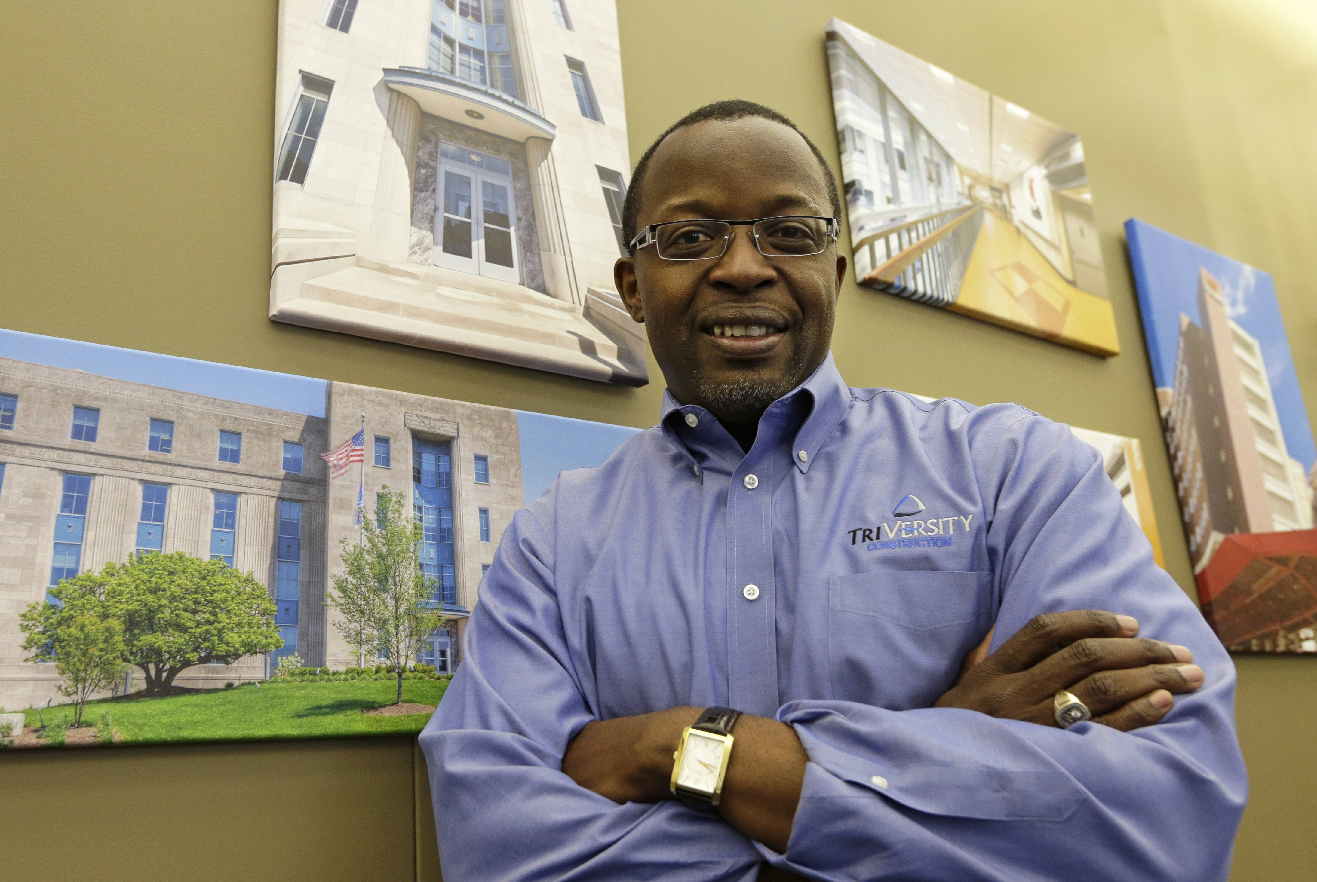 Mel Gravely, president of TriVersity Construction, poses in his office in front of some paintings of work his company has done, Wednesday, April 16, 2014, in Cincinnati. Gravely's company joined a program called a minority business accelerator even before he bought a controlling interest in the Cincinnati-based company in 2006. It helped the company get started and win contracts that have helped TriVersity's revenue double.