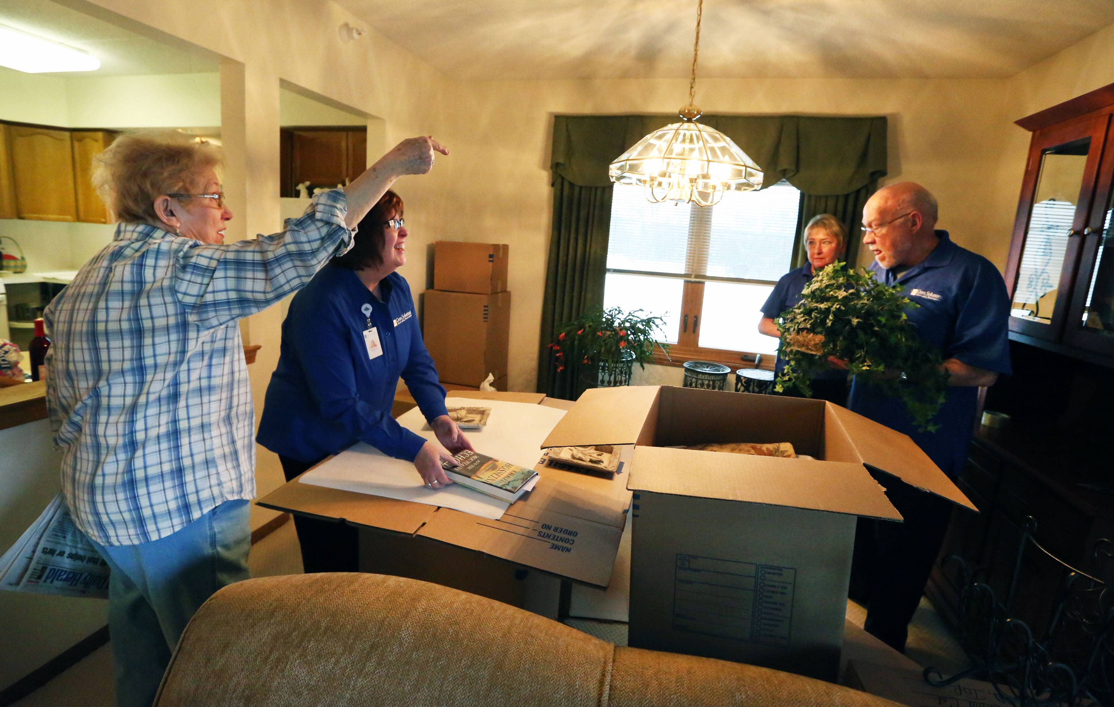 Martha Little of Des Plaines ask a question to senior move manager Sharon Moffat with Gero Solutions, far right corner, while the company packs items in her apartment in Des Plaines for a move to a retirement community.