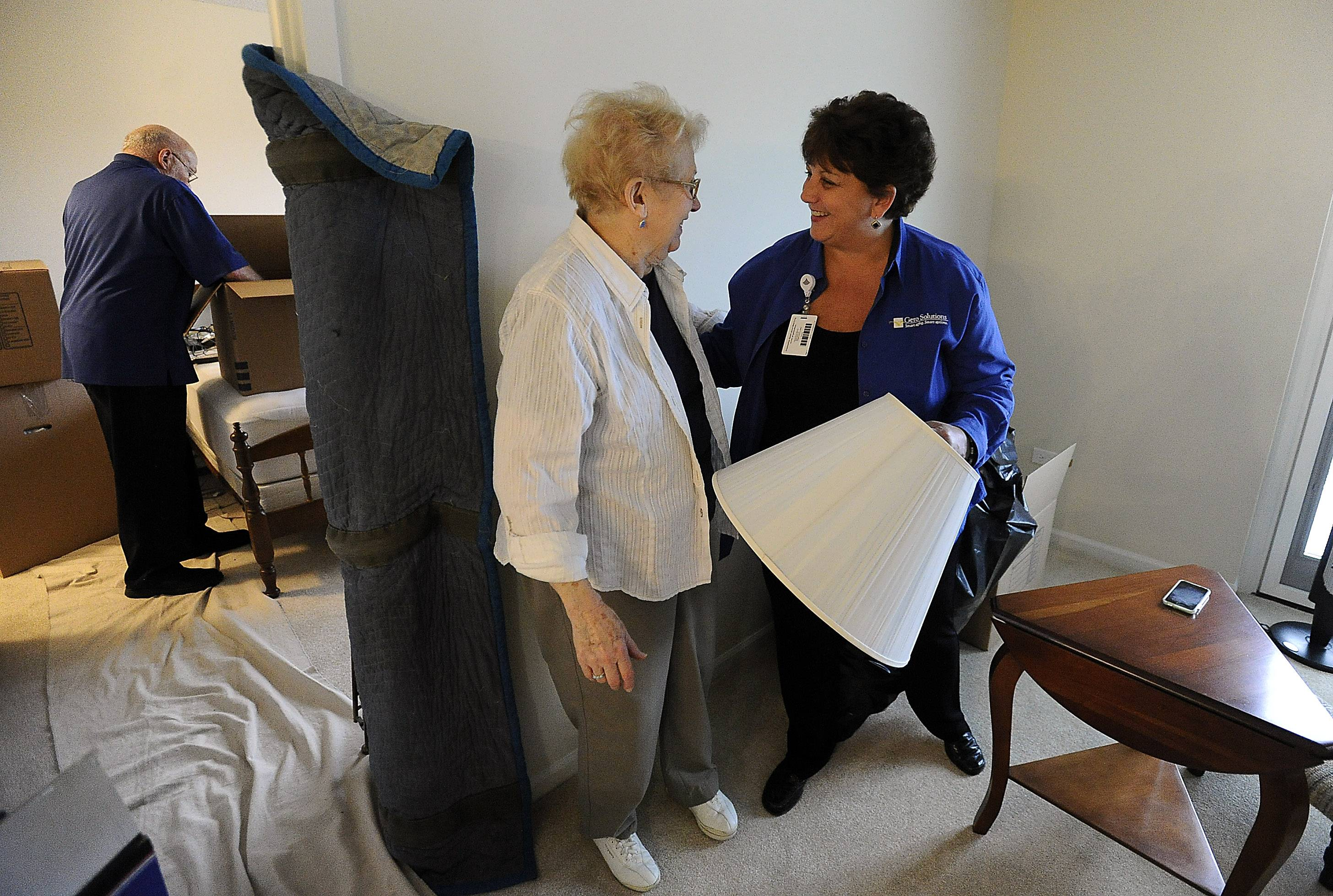 Gloria Bersani, director of Gero Solutions, talks with Martha Little as movers from Moore Moving get her settled into her new apartment at The Moorings in Arlington Heights.