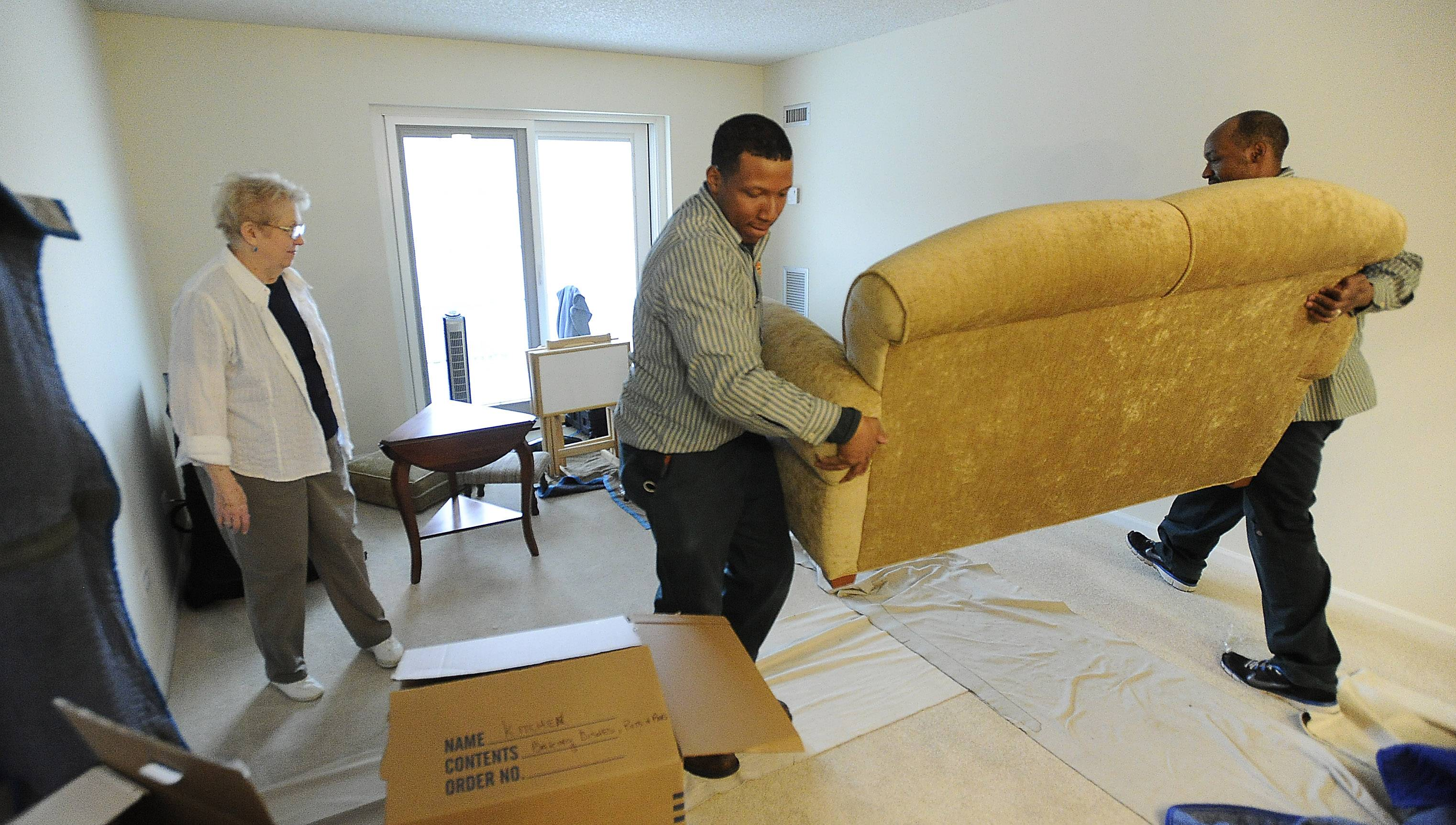 Martha Little watches as movers from Moore Movers position her couch into her new apartment at The Moorings in Arlington Heights.