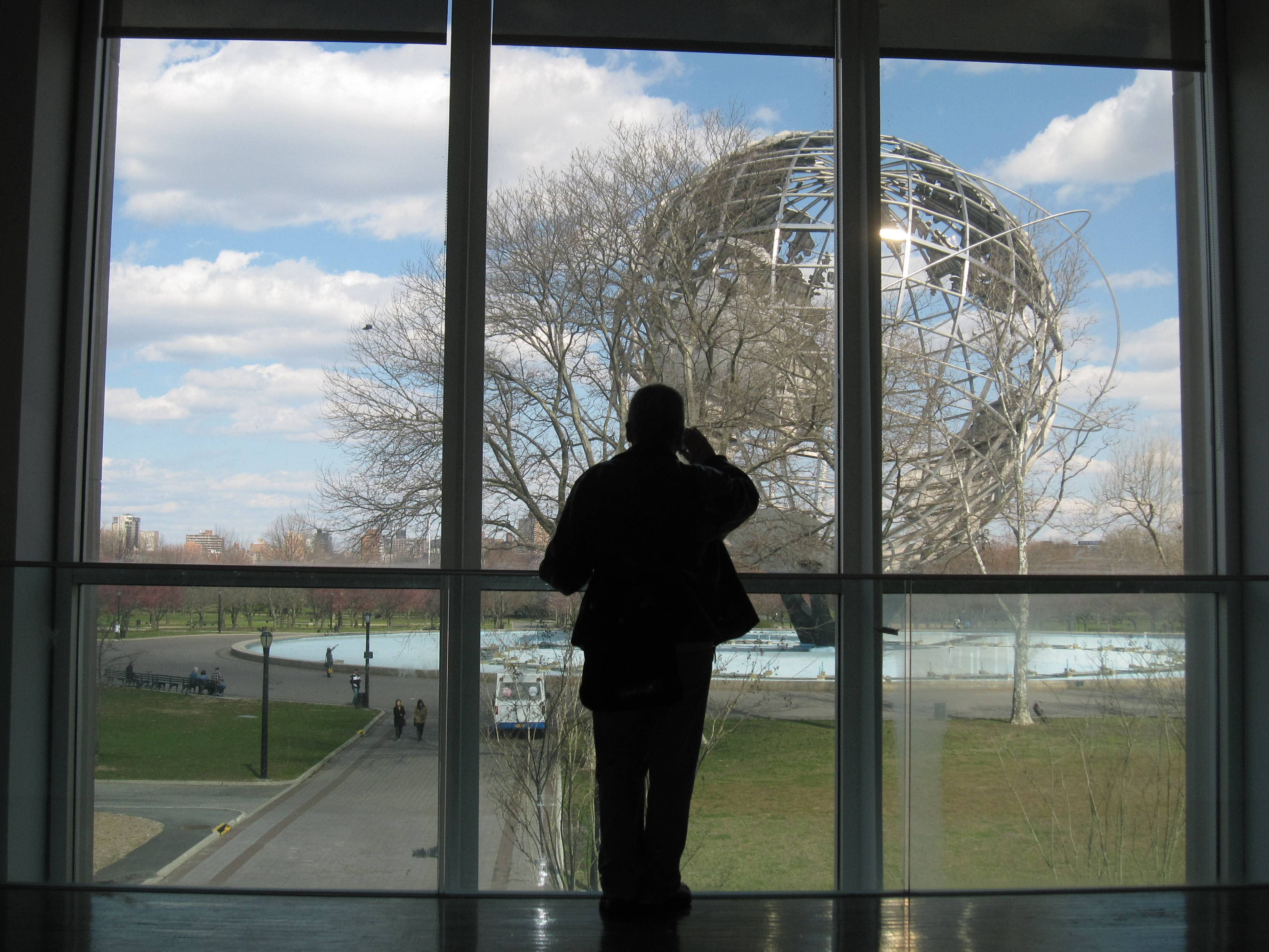 A visitor to the Queens Museum of Art takes a photo of the Unisphere through the museum windows in the Queens borough of New York.