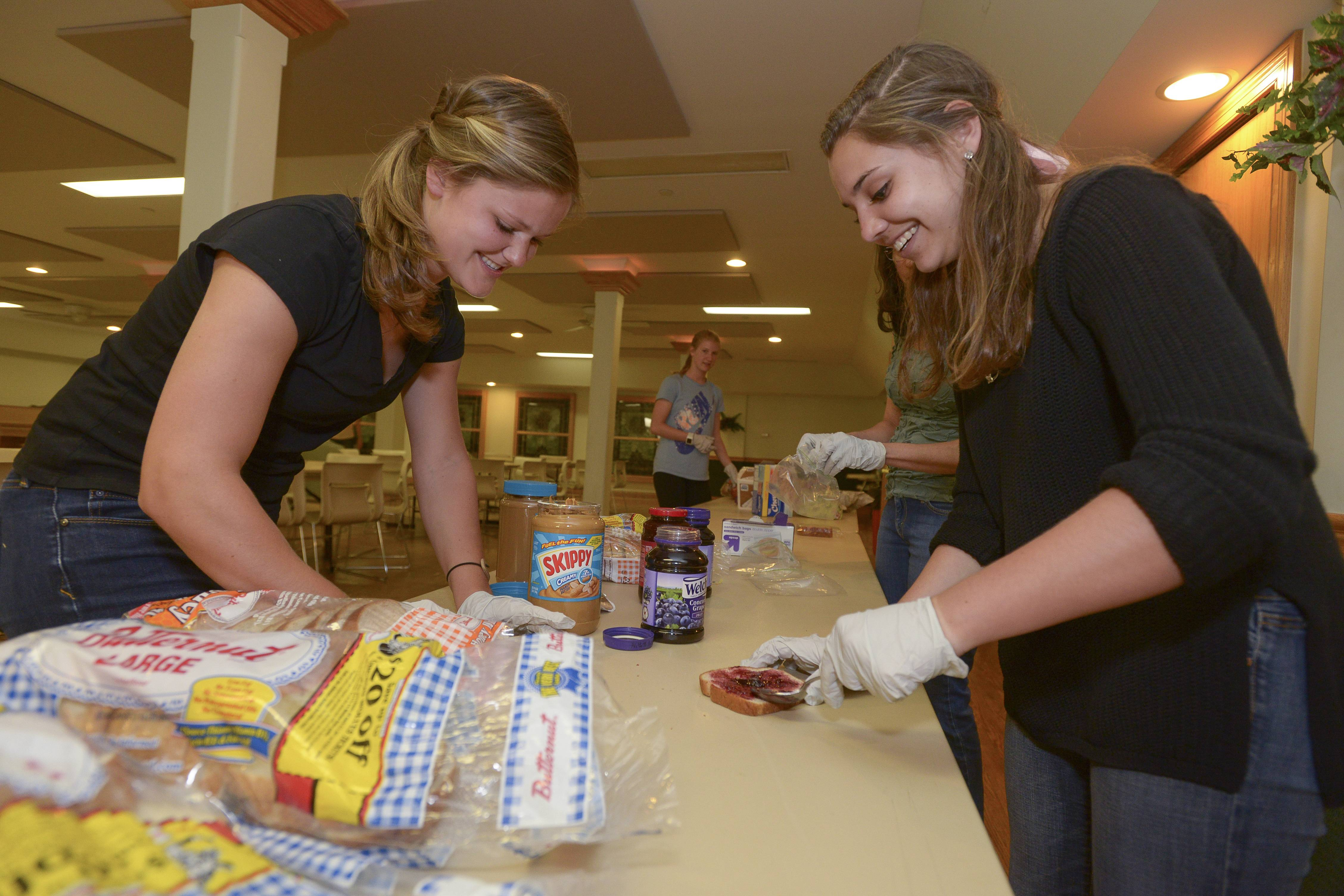 Members of the Daily Herald Leadership Team members Katie Mann, 18, of Wheaton Academy and Meg Maloney, 18, of Glenbard West High School make lunch sandwiches while volunteering Sunday at the Community United Methodist Church's PADS shelter in Naperville.