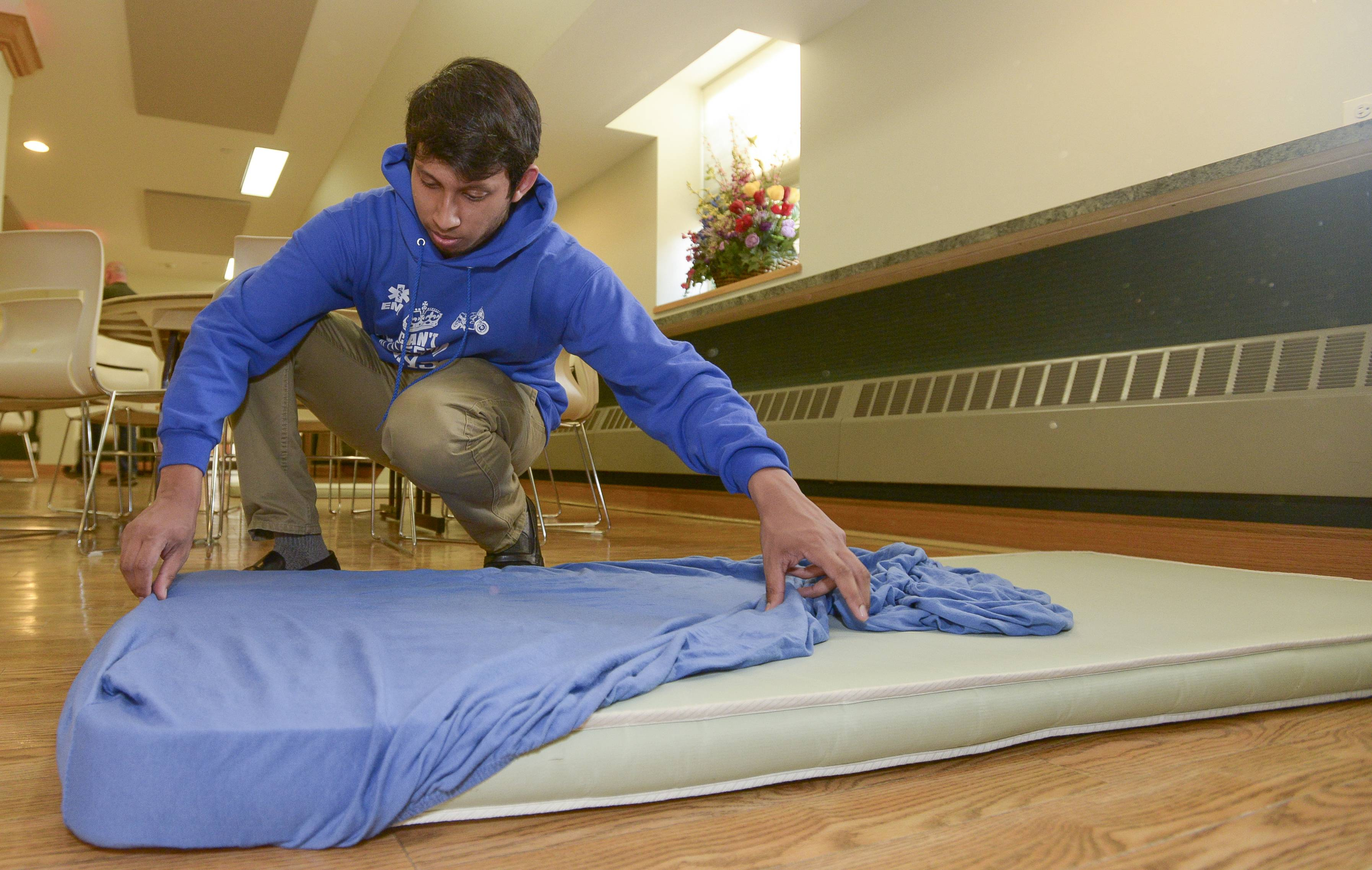 Daily Herald Leadership Team member Silas Ferrao of Naperville Central helps make up beds while volunteering Sunday at the Community United Methodist Church's PADS shelter in Naperville.