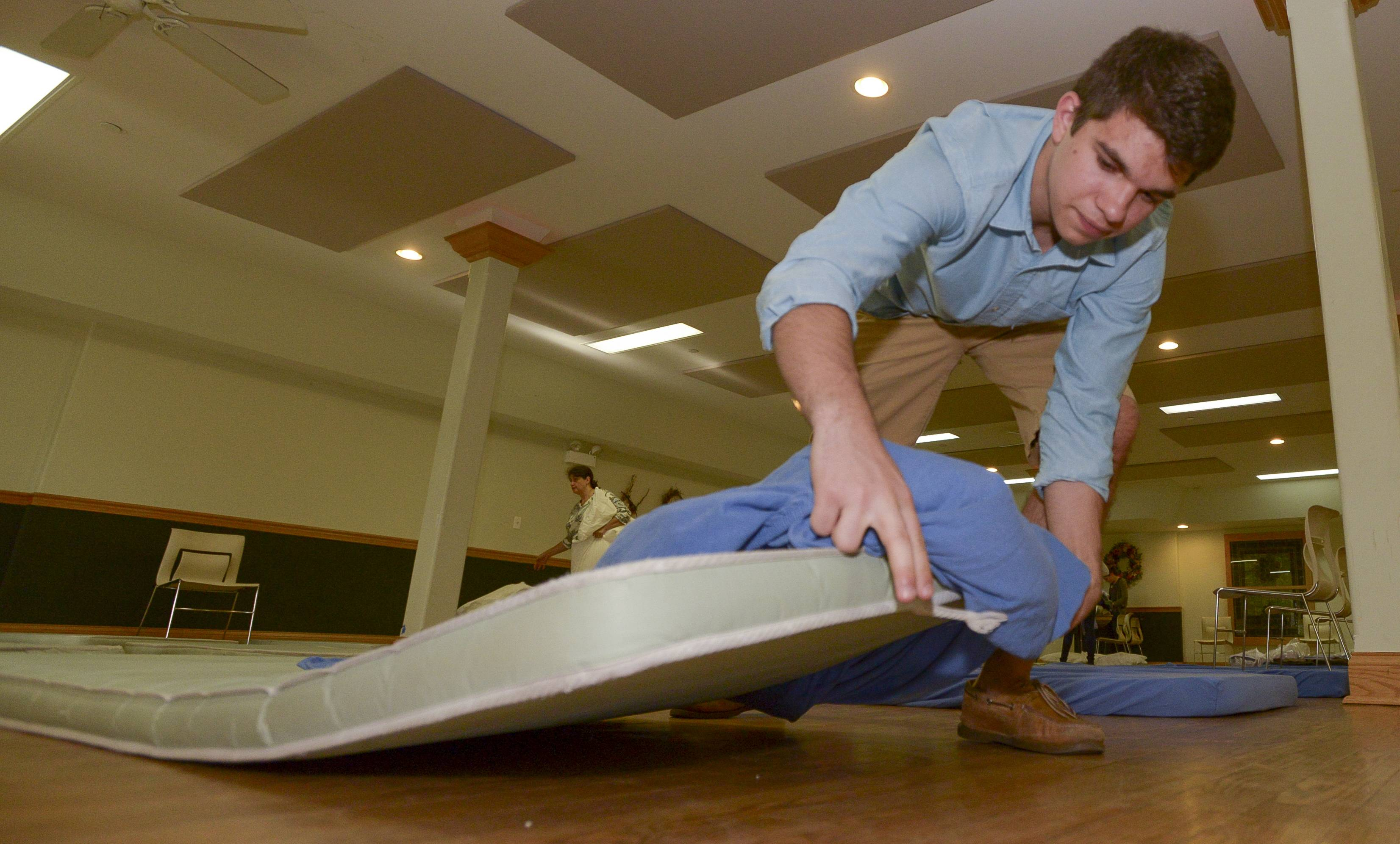 Daily Herald Leadership Team member Austin Hansen, 18, of Naperville North High School helps make up beds while volunteering Sunday at the Community United Methodist Church's PADS shelter in Naperville.