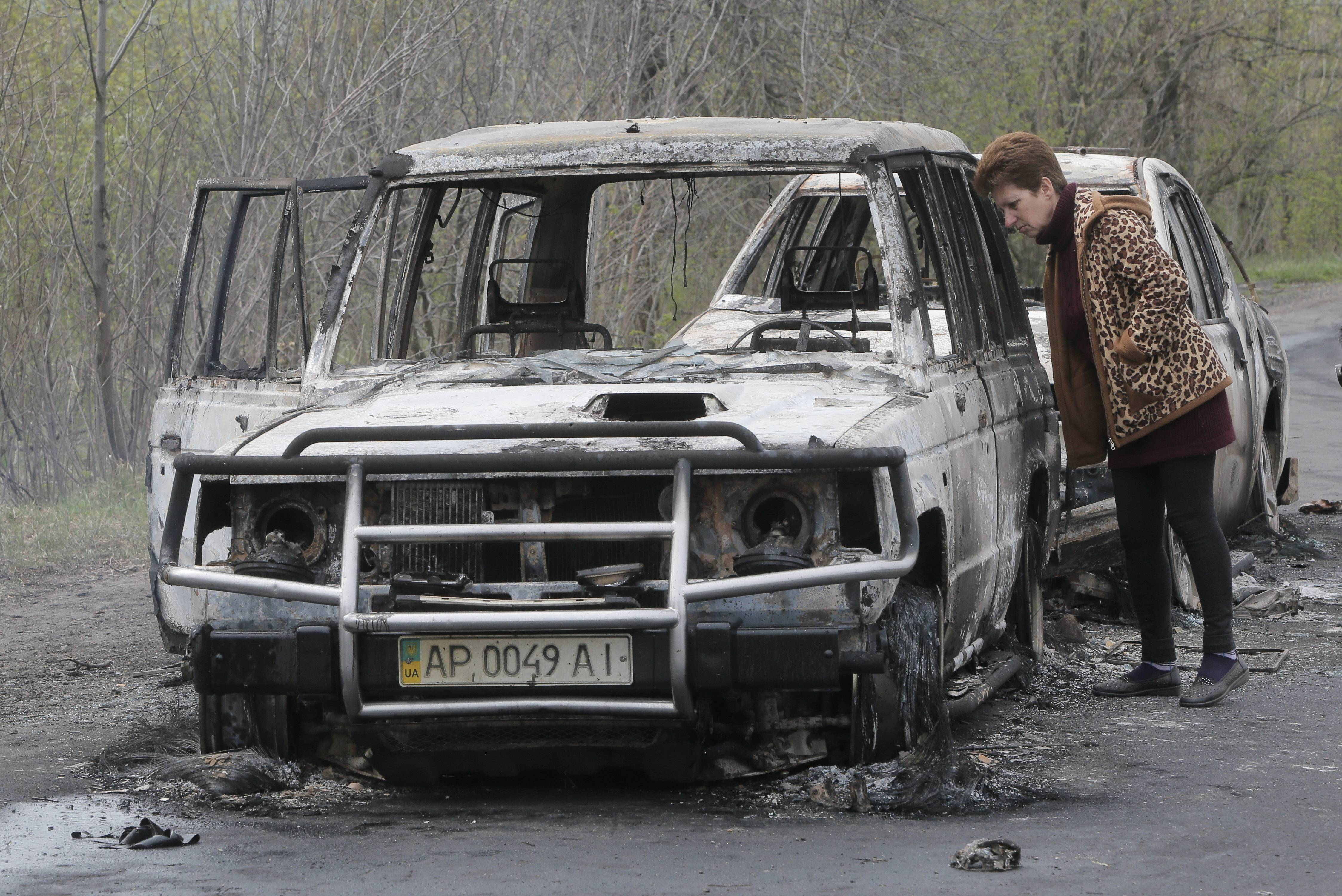 A local resident inspects burnt-out cars after night fight at the checkpoint which was under control of pro-Russian activists in the village of Bulbasika near Slovyansk on Sunday.