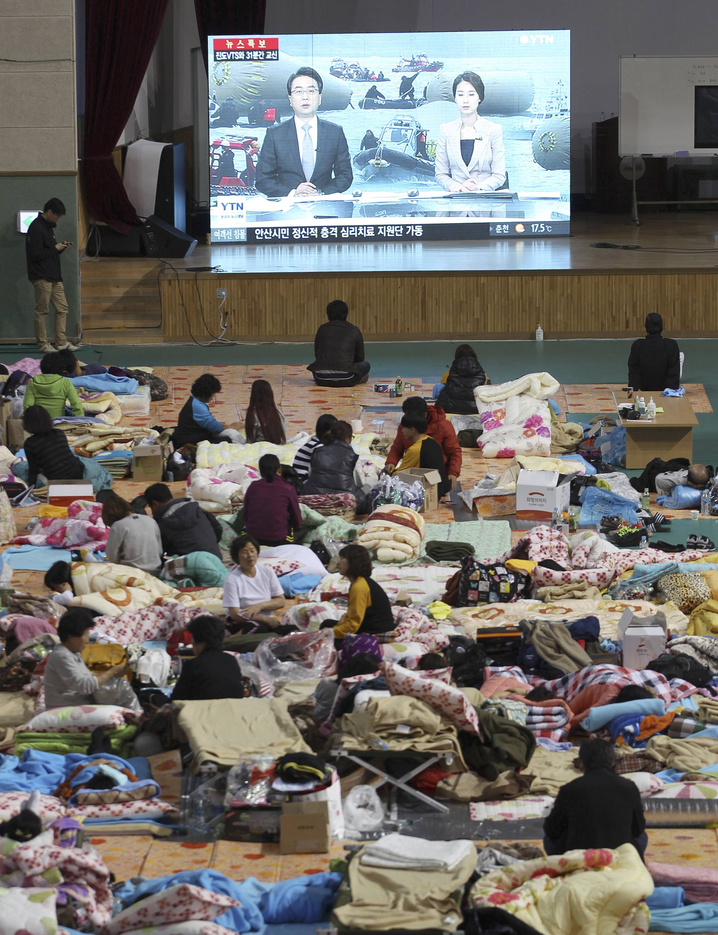 Relatives of missing passengers, waiting in a school gymnasium in Jindo, South Korea, watch a TV news program reporting government's rescue operations Sunday. After more than three days of frustration and failure, divers on Sunday finally found a way into the submerged ferry.