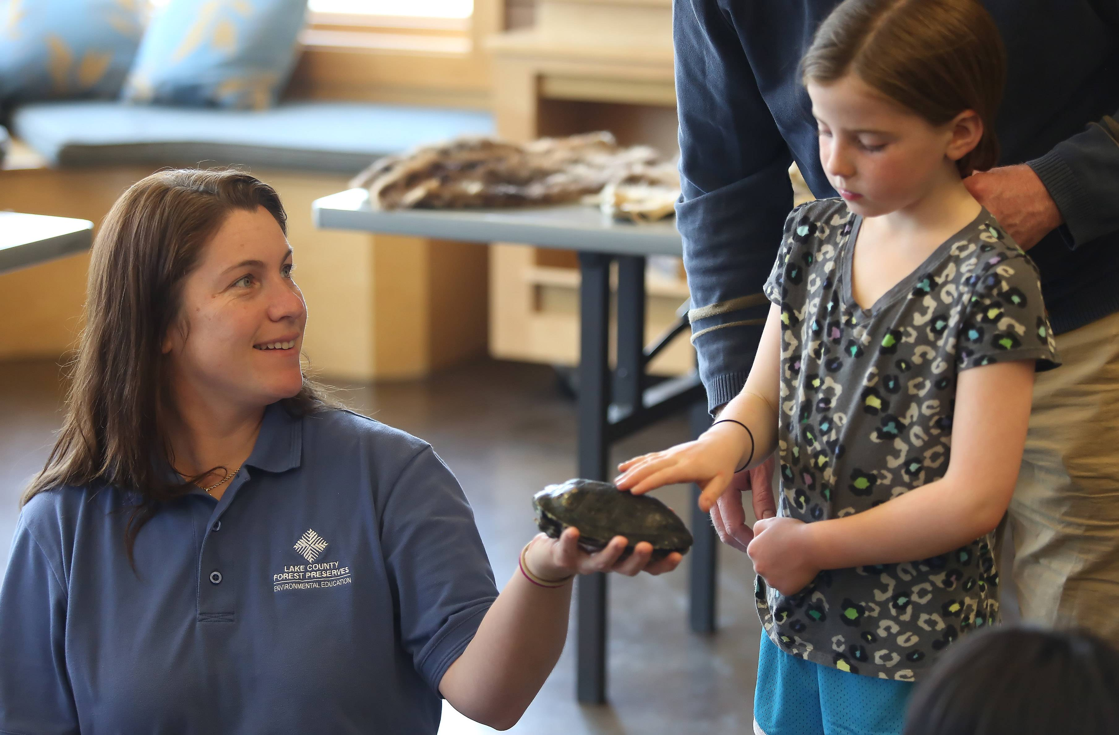 Environmental educator Melissa Alderson holds a turtle for Ella Kennedy, 8, of Libertyville to touch during the Greet Education Animals program Sunday hosted by the Lake County Forest Preserve District at Ryerson Conversation Area near Riverwoods. The event kicked off a week of programs celebrating Earth Day.