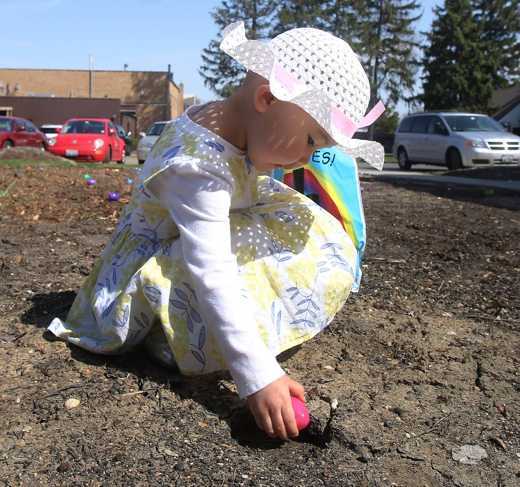 Two-year-old Jolene Tugs of Arlington Heights reaches down for an Easter egg during the Faith Lutheran Church Eggstravaganza event Easter Sunday in Arlington Heights. About 30 children searched for 850 eggs, worked on religious crafts, and listened to the story of Easter.