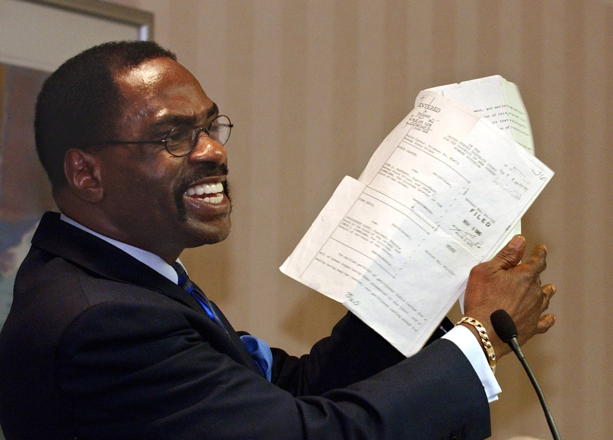 "Former boxer Rubin ""Hurricane"" Carter holds the writ of habeas corpus that freed him from prison, during a news conference in this Jan. 29, 2004, photo, Carter, who spent almost 20 years in jail after twice being convicted of a triple murder he denied committing, died at his home in Toronto on Sunday, according to long-time friend and co-accused John Artis. He was 76."