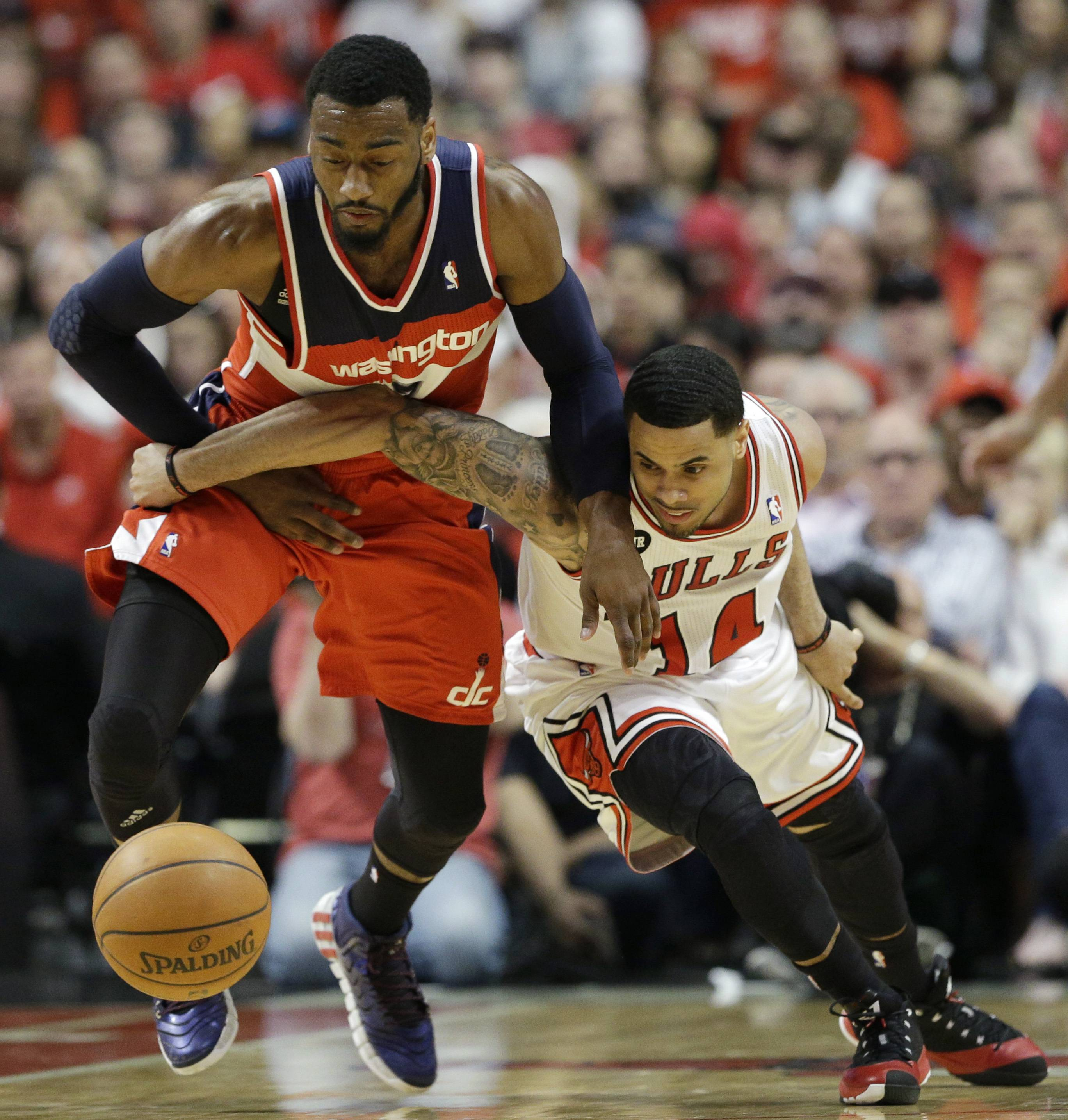 Washington Wizards guard John Wall, left, steals the ball from Chicago Bulls guard D.J. Augustin during the first half in Game 1 of an opening-round NBA basketball playoff series in Chicago, Sunday, April 20, 2014.