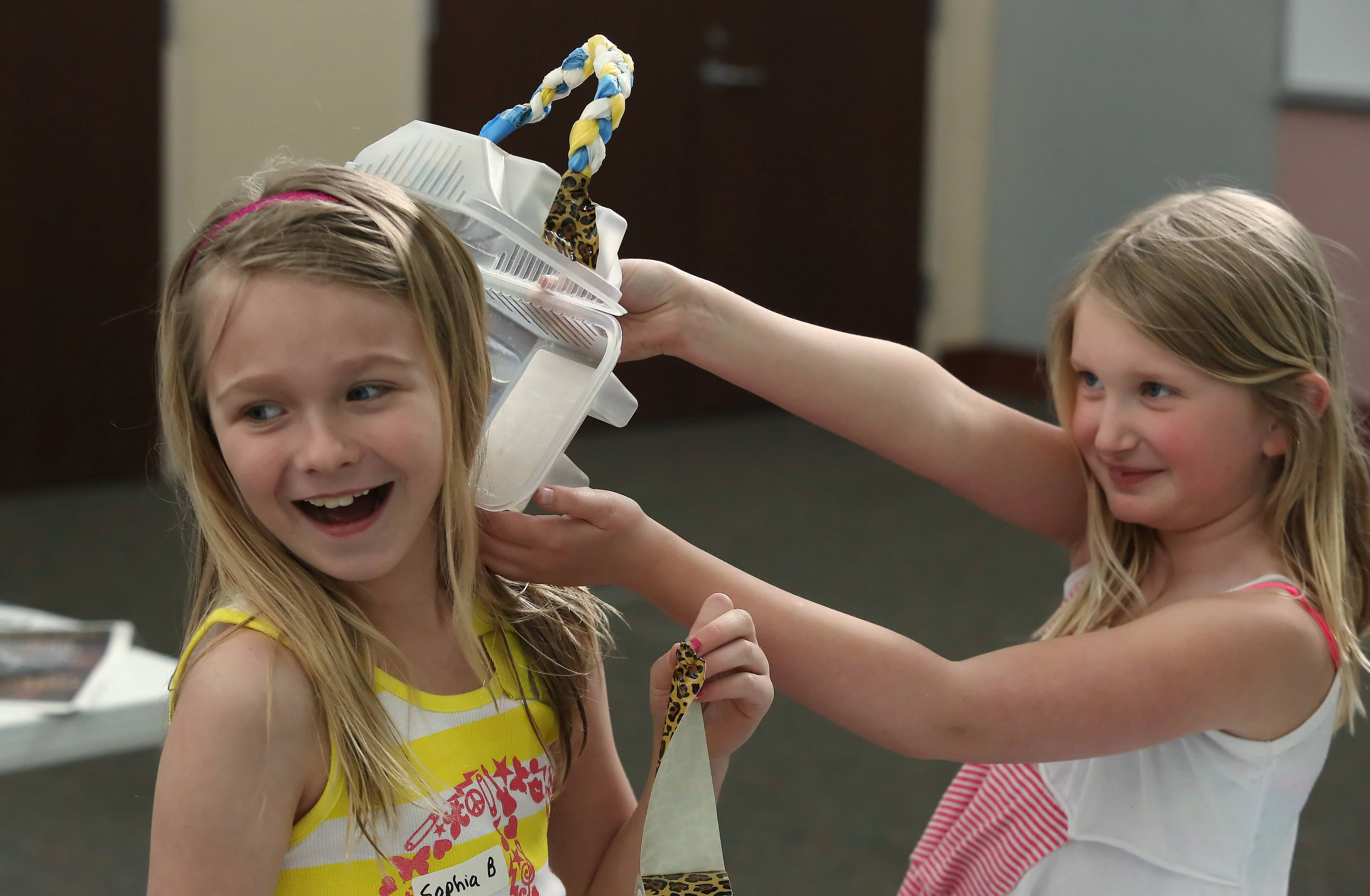 "Cas Yovino, right, has her purse attack Sophia Barszcz on Monday during the ""Eureka: Invent the Newest Fashion!"" program at the Lake Villa District Library. Children made dresses, backpacks, shoes and other items out of recycled material including newspaper, plastic bottles and plastic bags."