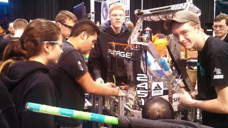 Fox Valley area PWNAGE Robotics team students work on a robot at the FIRST Midwest Regional competition April 5 in Chicago. From left are, McKenna Haller of Metea Valley High School, Jose Torres of West Aurora High School, and Emil Broemmelsiek and Nick Bowgren, both of Batavia High School.