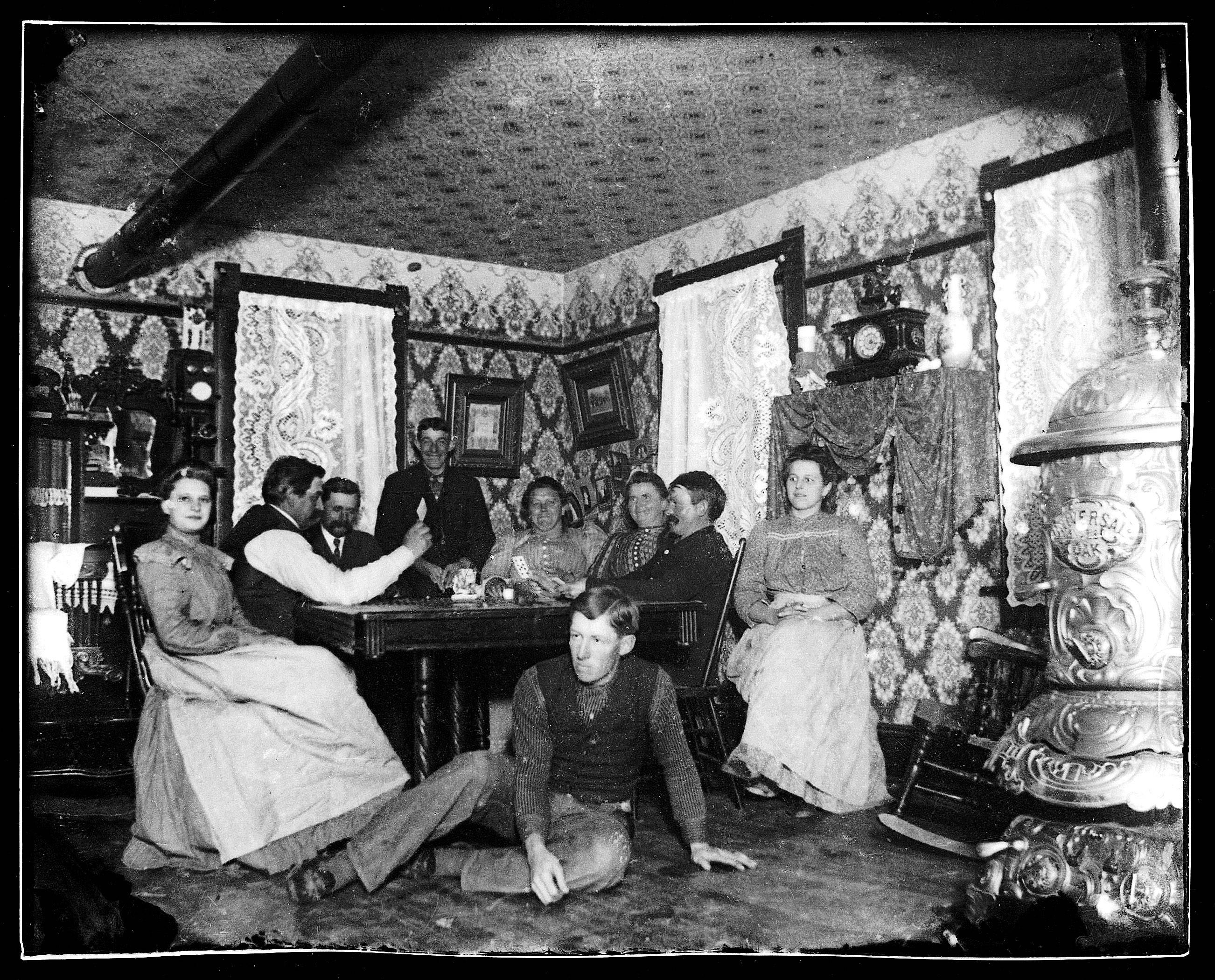 Early 1900s in the living room of the Pfingsten Farm home in Schaumburg. Fred Pfingsten, in the foreground, also took the picture. The camera was set on a fixed object. Some flash powder was given a length of fuse, the room was darkened, camera shutter was opened, fuse was ignited, and Fred would then dash over and sit on the floor until flash powder was ignited. The camera shutter would then be closed.