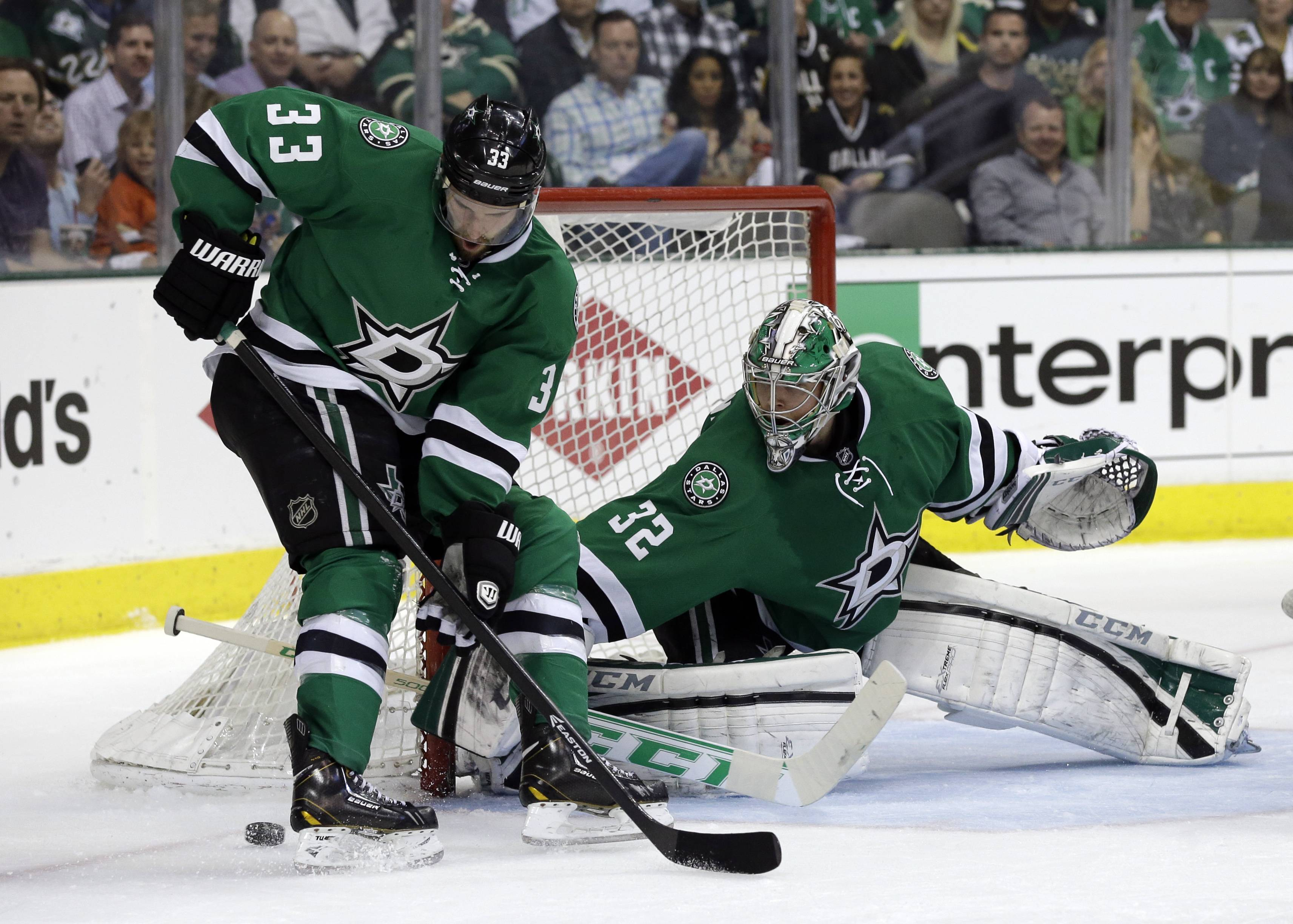Dallas Stars' Alex Goligoski (33) helps goalie Kari Lehtonen (32) of Finland clear the puck away from the net during the second period of Game 3 of a first-round NHL hockey Stanley Cup playoff series game against the Anaheim Ducks, Monday, April 21, 2014, in Dallas.