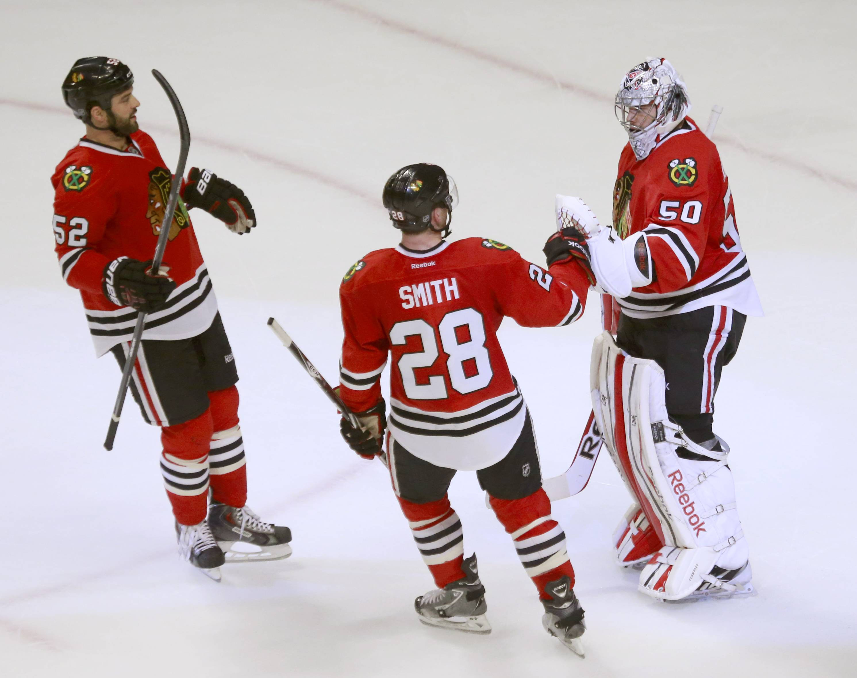 Blackhawks goalie Corey Crawford (50) celebrates with Brandon Bollig (52) and Ben Smith after the Blackhawks' 2-0 win over the St. Louis Blues in Game 3 of a first-round NHL hockey Stanley Cup playoff series game Monday, April 21, 2014, in Chicago.