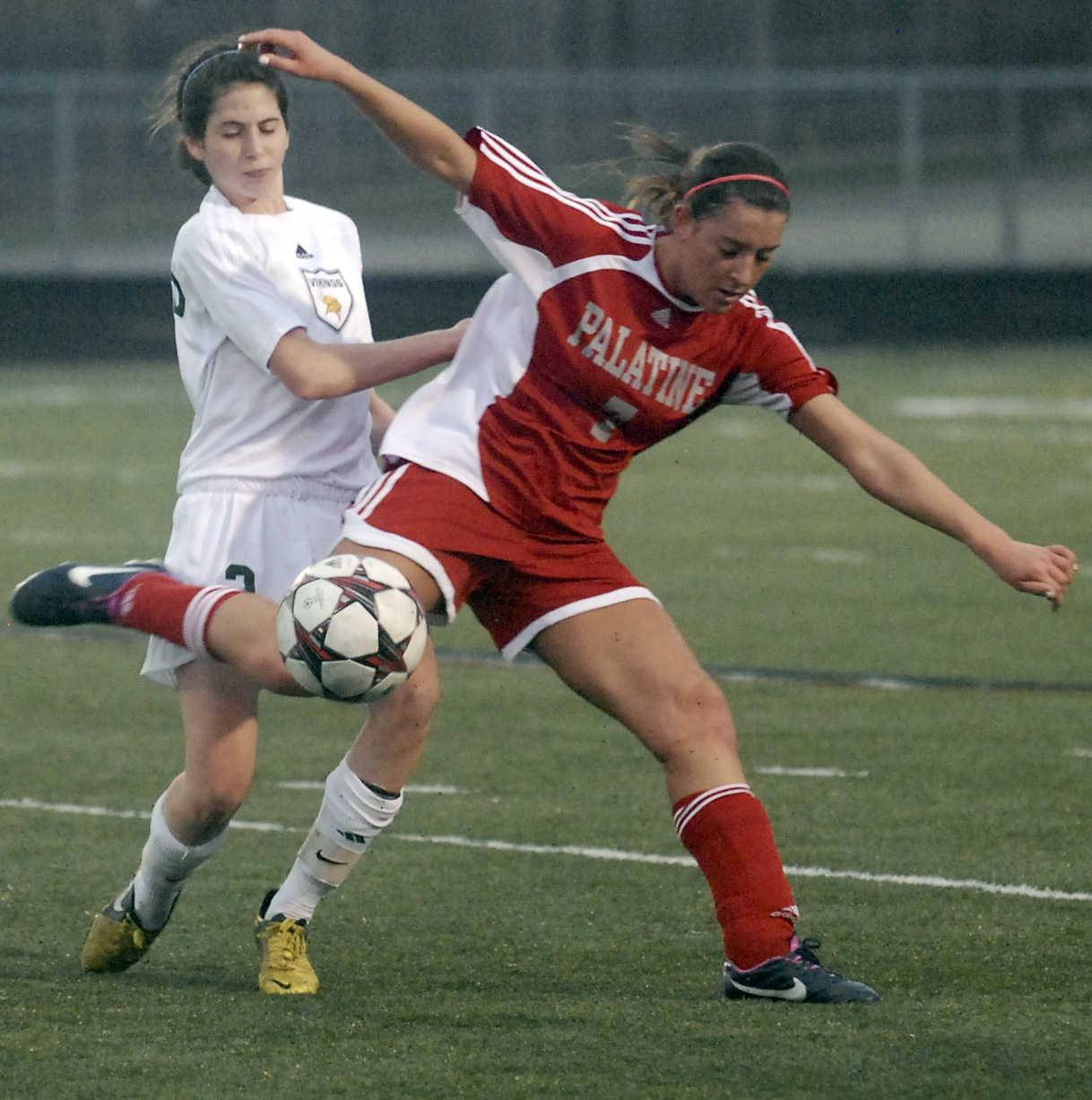 Palatine's Michelle Raymond, right, battles Fremd's Jessica Kopec for possession on Monday at Hale Hildebrandt Field.