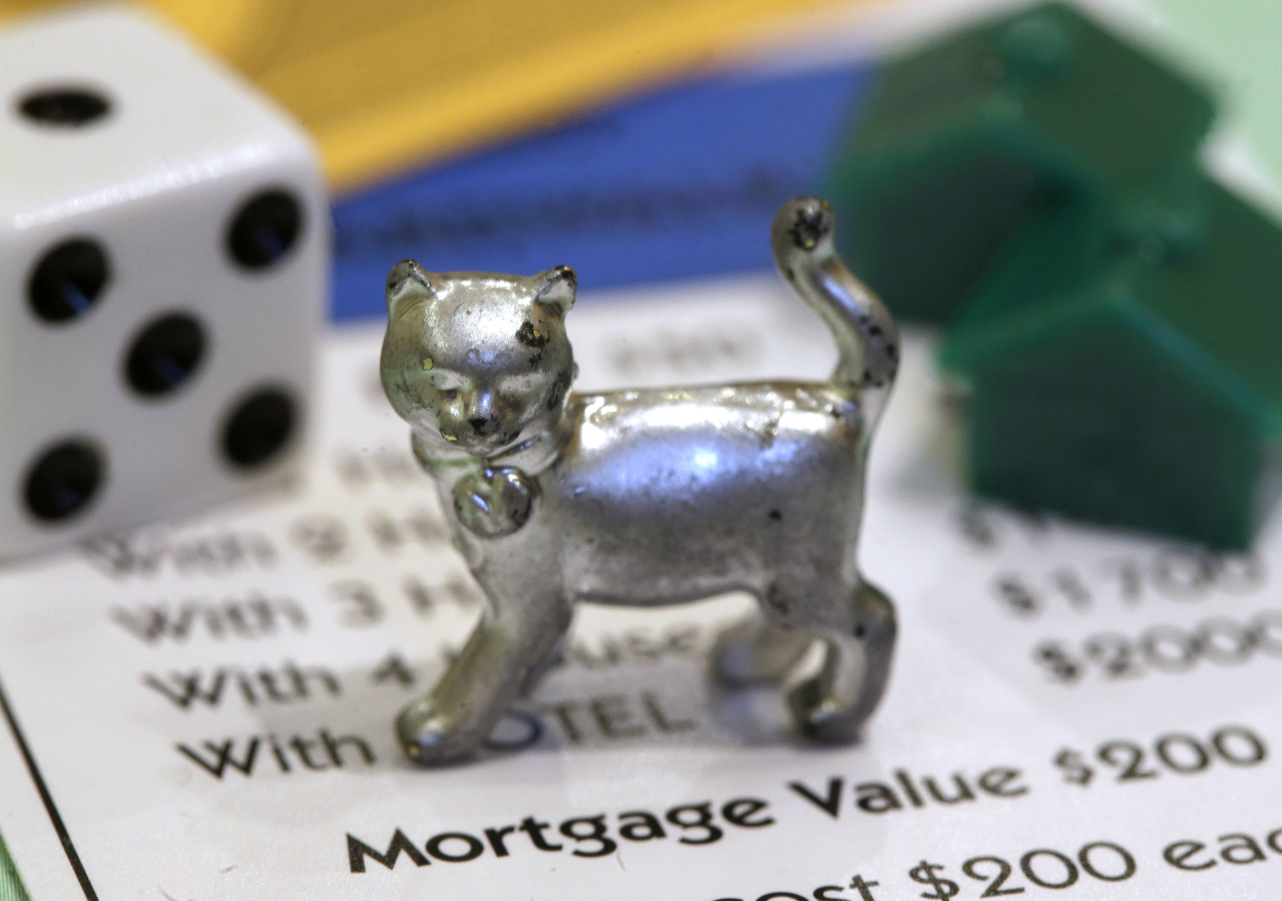 The cat Monopoly token on a Boardwalk deed next to a die and houses at Hasbro Inc. headquarters, in Pawtucket, R.I.