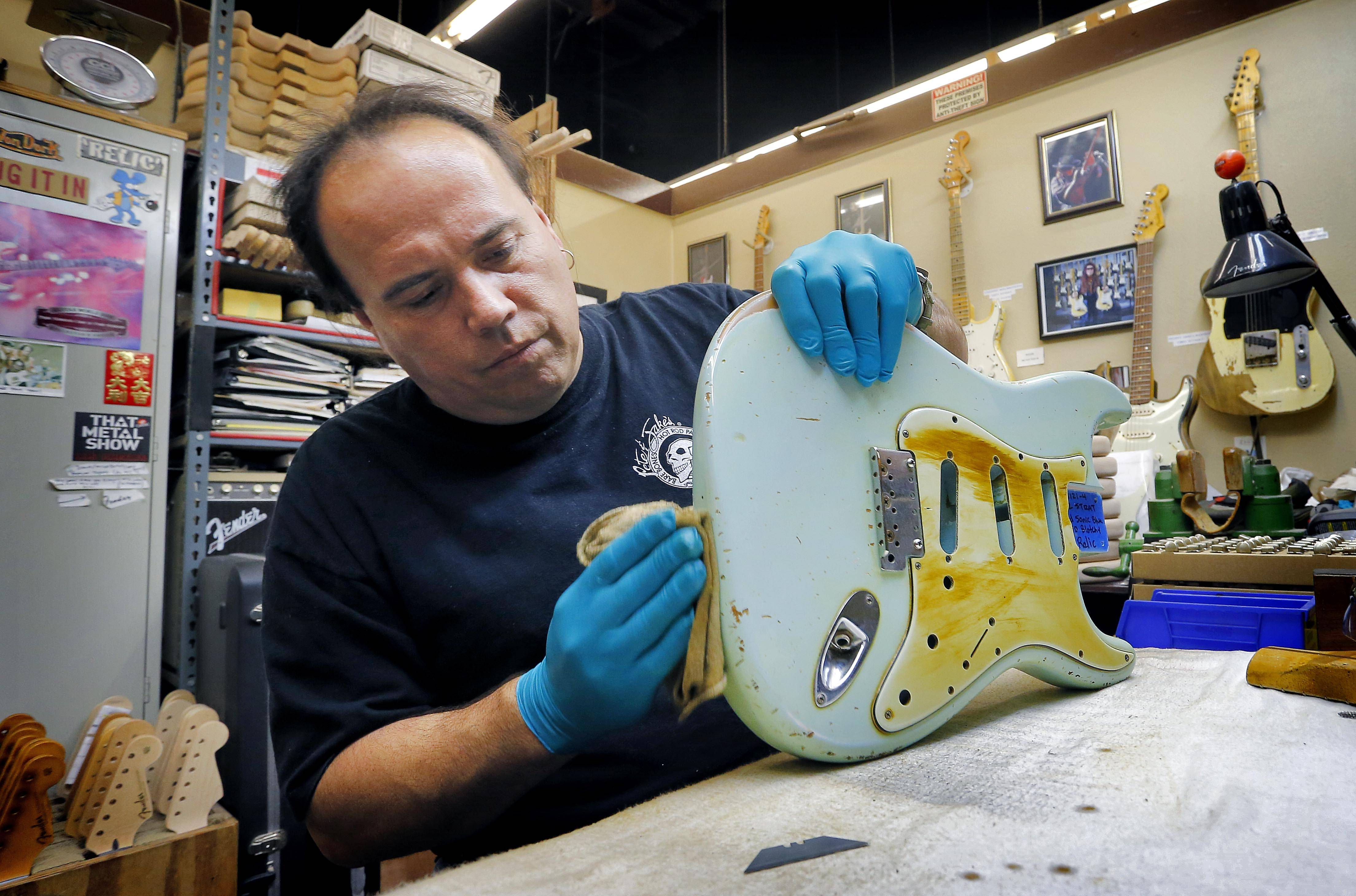 Fender Custom Shop Master Builder John Cruz works on a heavily-used Fender Stratocaster body at the Fender factory in Corona, Calif. Leo Fender developed the instrument in a small workshop in Fullerton, Calif. six decades ago.