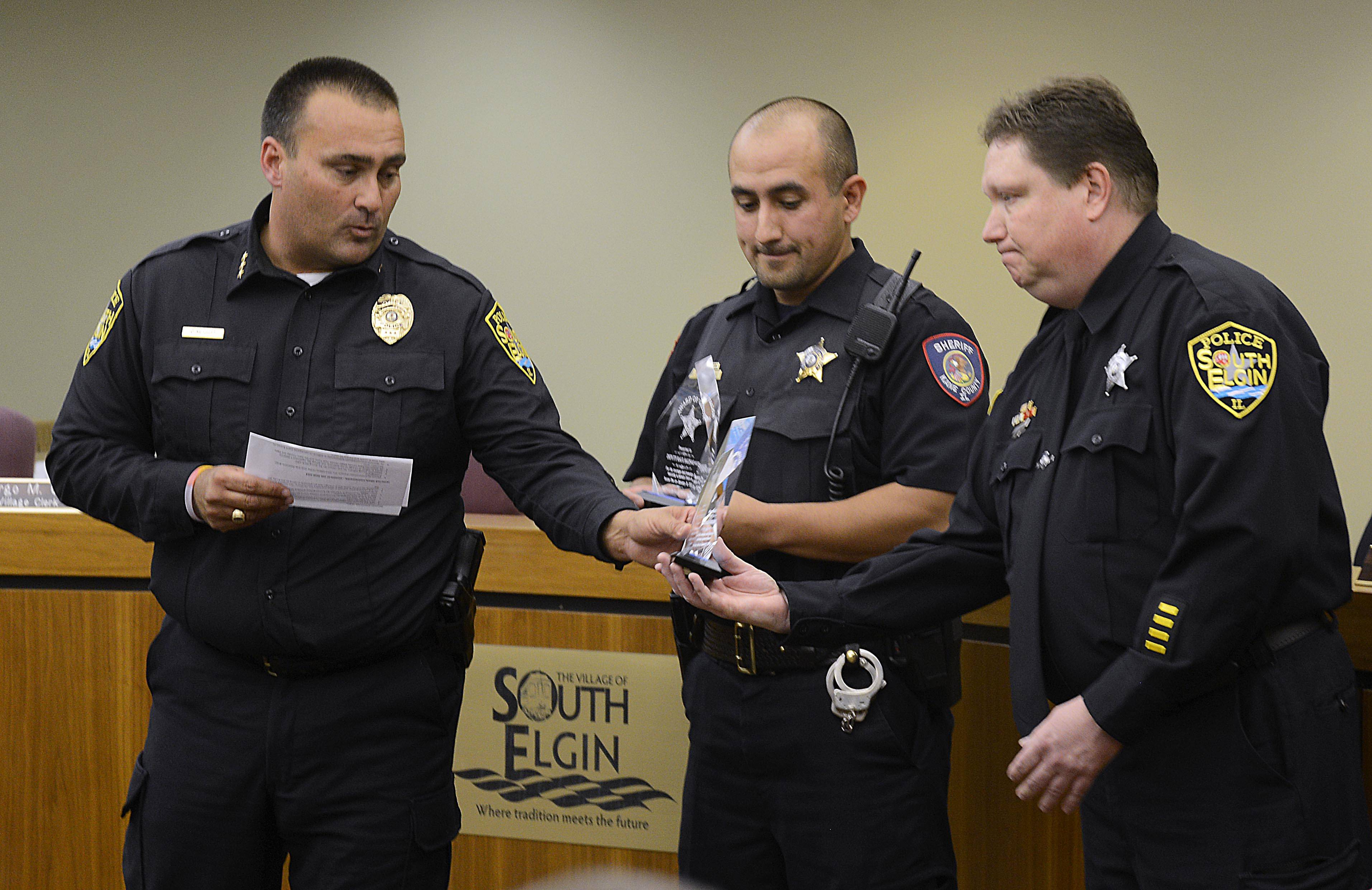 South Elgin Police Chief Christopher Merritt gives a Valor Award to police officer Roger Isham, right, as Kane County sheriff's deputy Raul Salinas holds his Monday night at the village board meeting. They responded separately to a house fire last year and together saved the life of a woman in a wheelchair who was trapped.