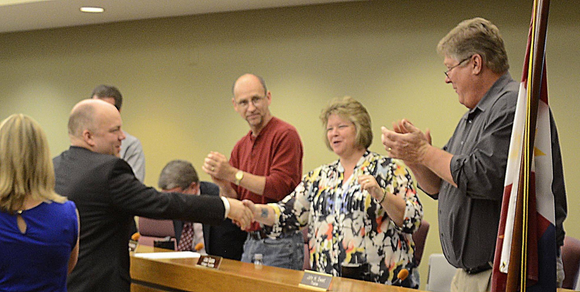 South Elgin police detective Brian Polkinghorn shakes hands with village board members after he was named Officer of the Year Monday night at the village board meeting.