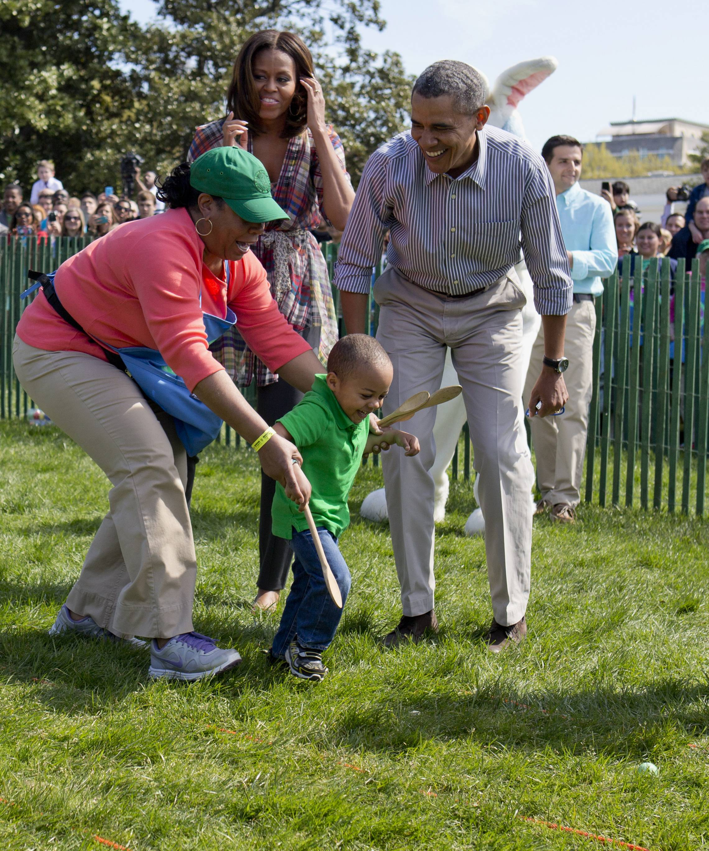 President Barack Obama and first lady Michelle Obama cheer a little egg roller as they host the White House Easter Egg Roll on the South Lawn of the White House Monday.