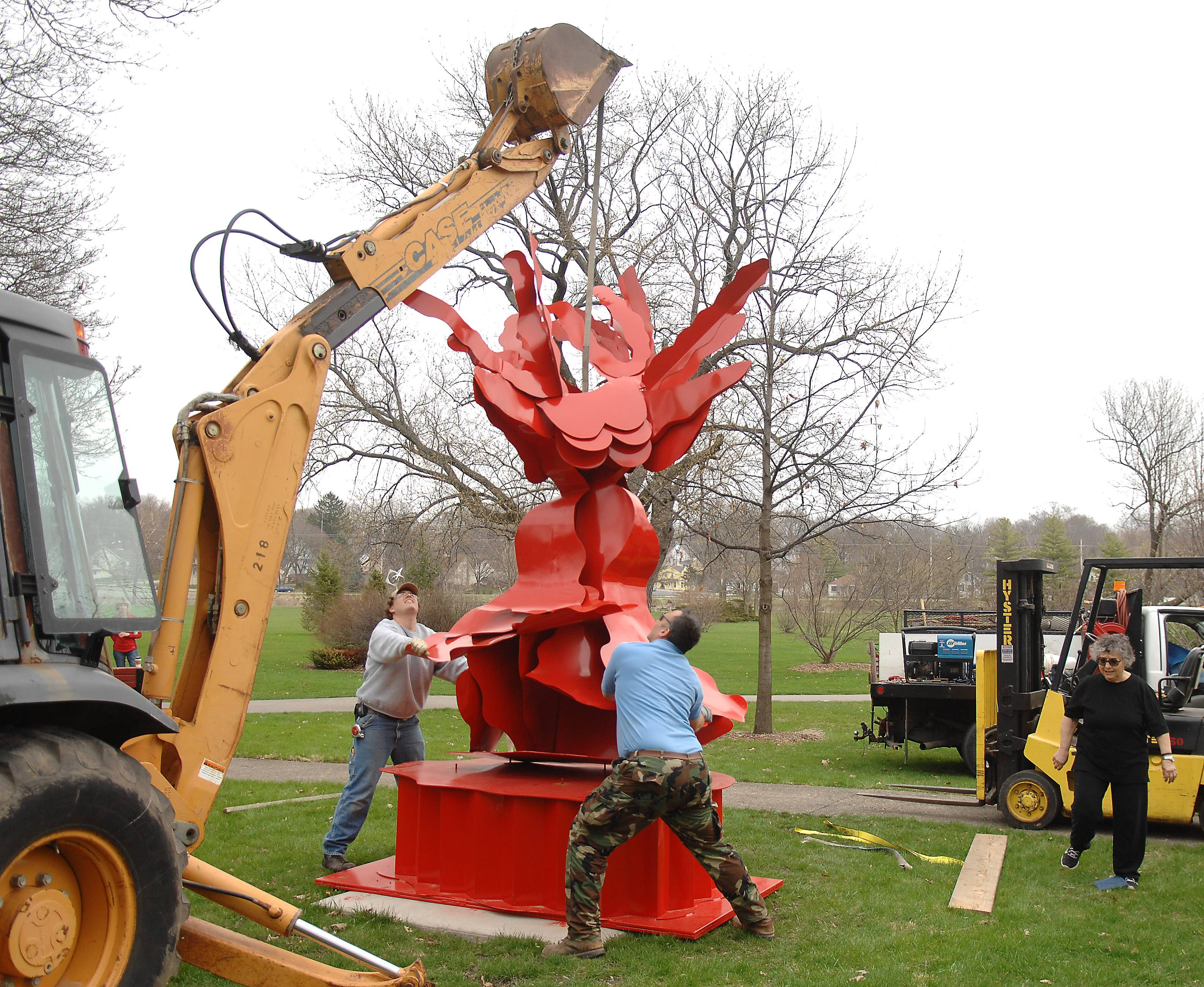 "St. Charles Park District employees Alex DeSimone, left, and John Kish guide Ruth Aizuss Migdal's sculpture on to its base at Mount St. Mary Park Monday as part of the 9th annual Sculpture in the Park exhibit. The stainless steel piece is titled, ""Here,"" and weighs in at around 2.5 tons."