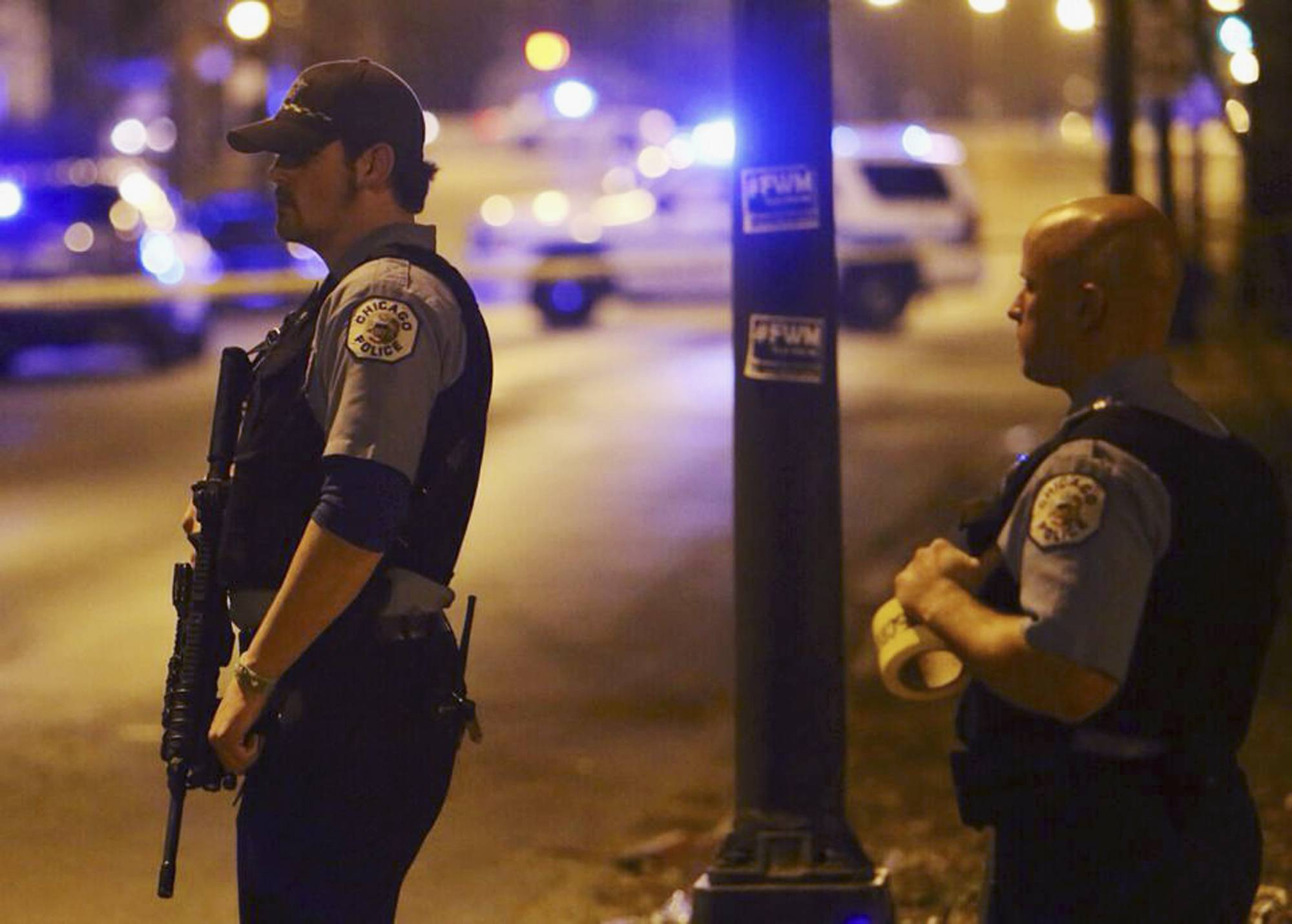 Police stand guard at the scene where five children, all 15 or younger, were shot and wounded Sunday as they walked from a park in Chicago.