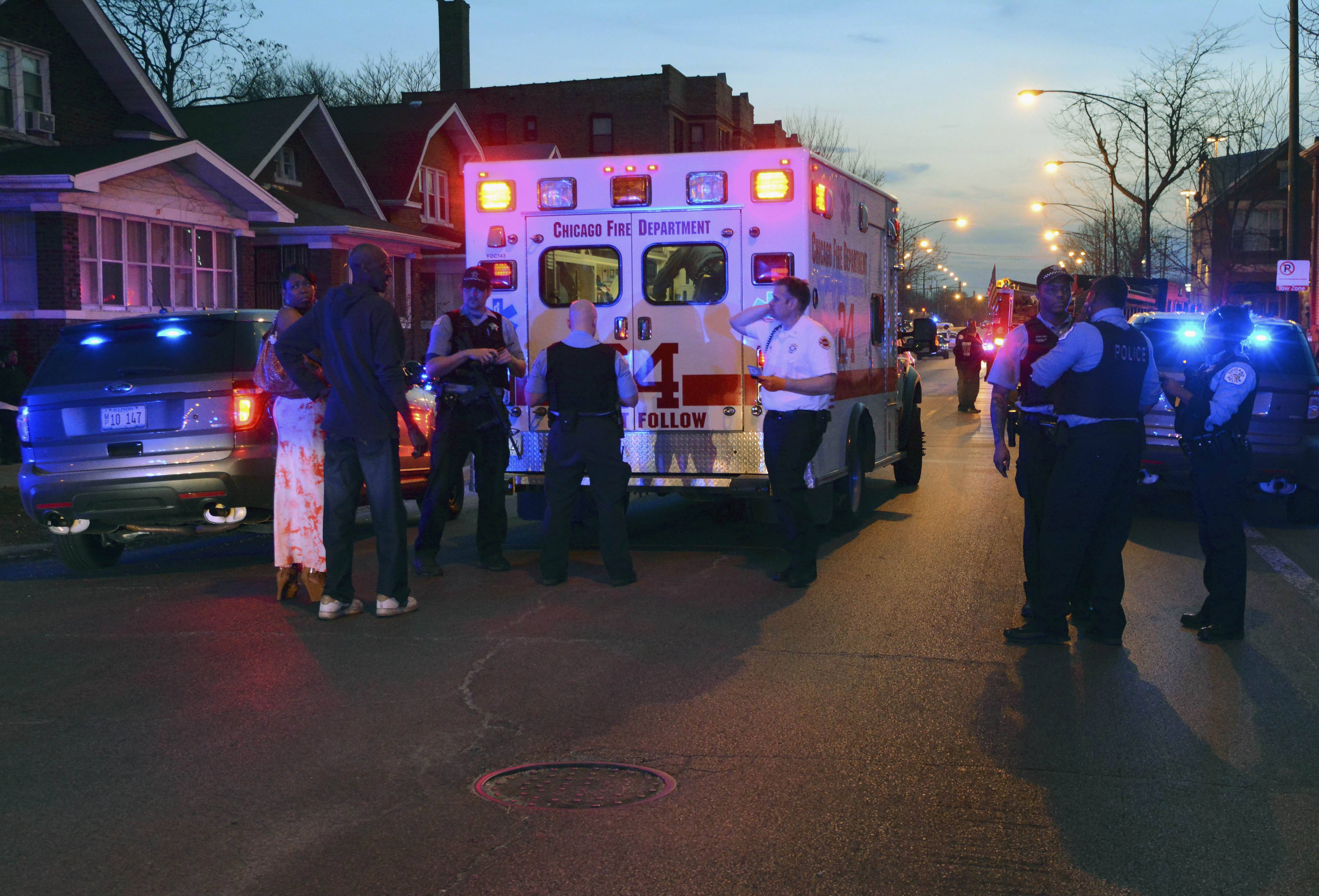Chicago police and fire department personnel gather at the scene where five children were shot and wounded Sunday. Eight people were killed and 44 injured in gun violence over the weekend.