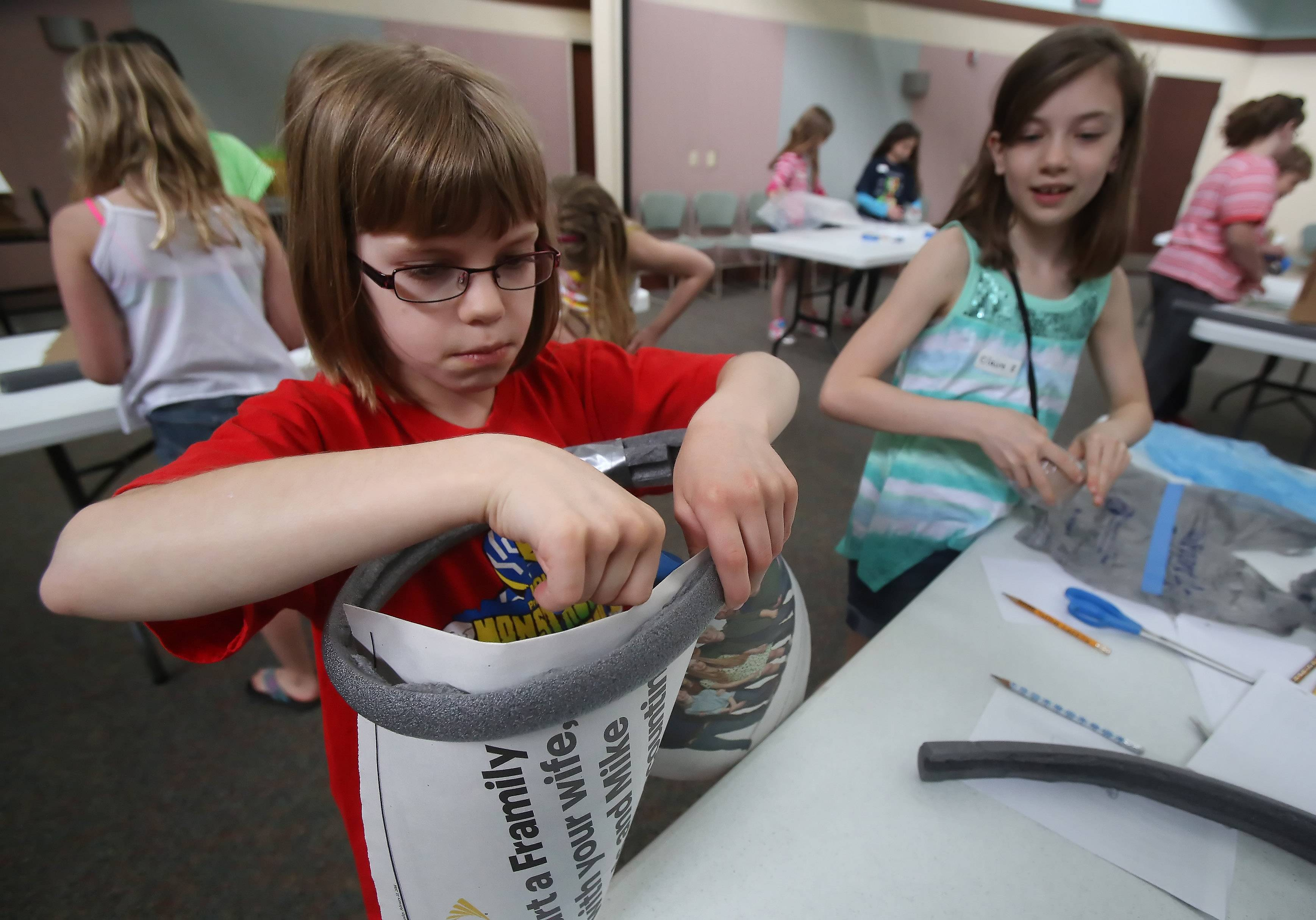 "Emma Silk, left, and Claire Zutkis, both 9, make dresses out of newspaper and insulation tubing Monday during the ""Eureka: Invent the Newest Fashion!"" program at the Lake Villa District Library. Children made dresses, backpacks, shoes and other items out of recycled material such as newspaper, plastic bottles and plastic bags."