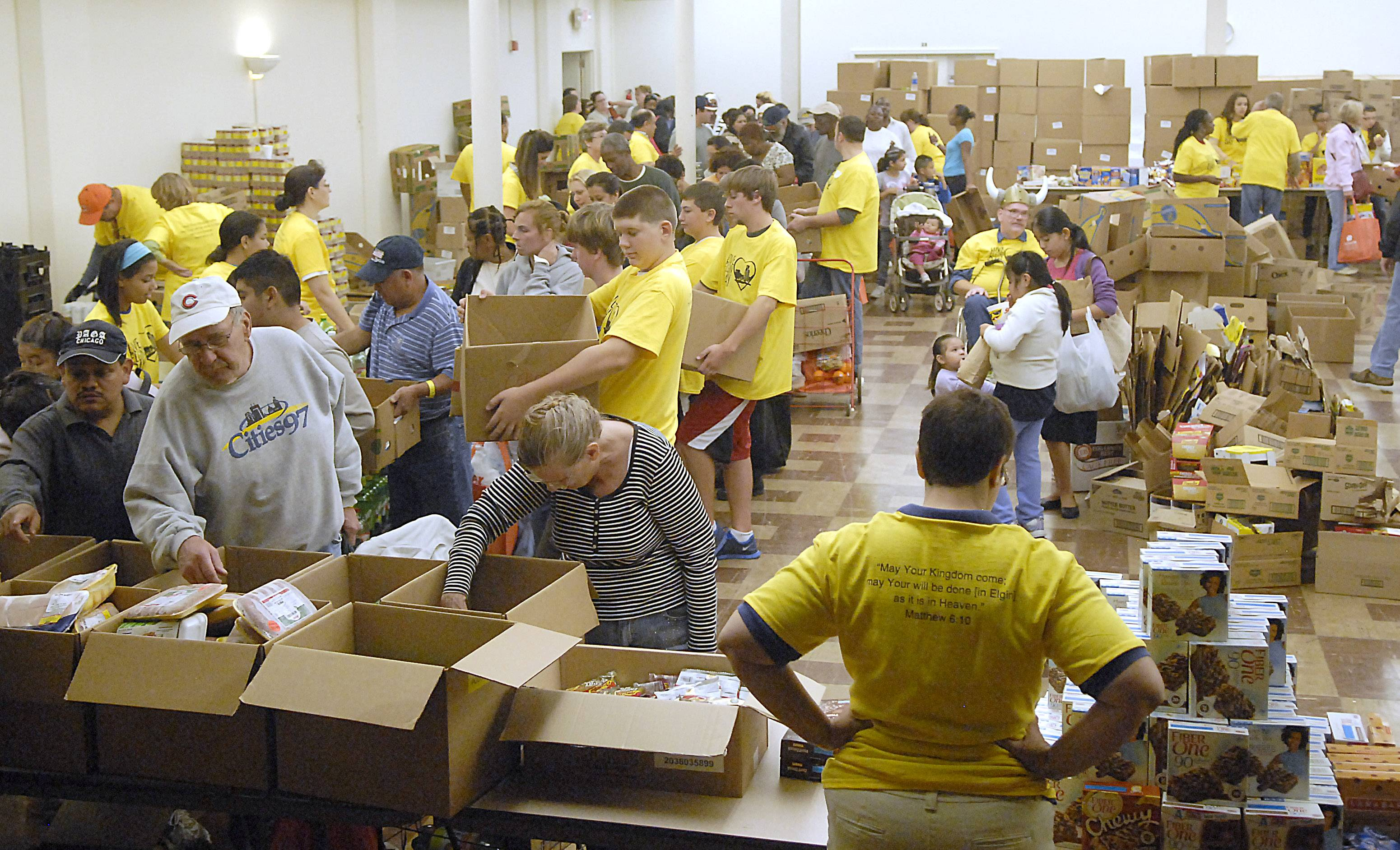 Volunteers in yellow shirts help people gather free groceries in the basement of the First United Methodist Church on Love Elgin Day last September.