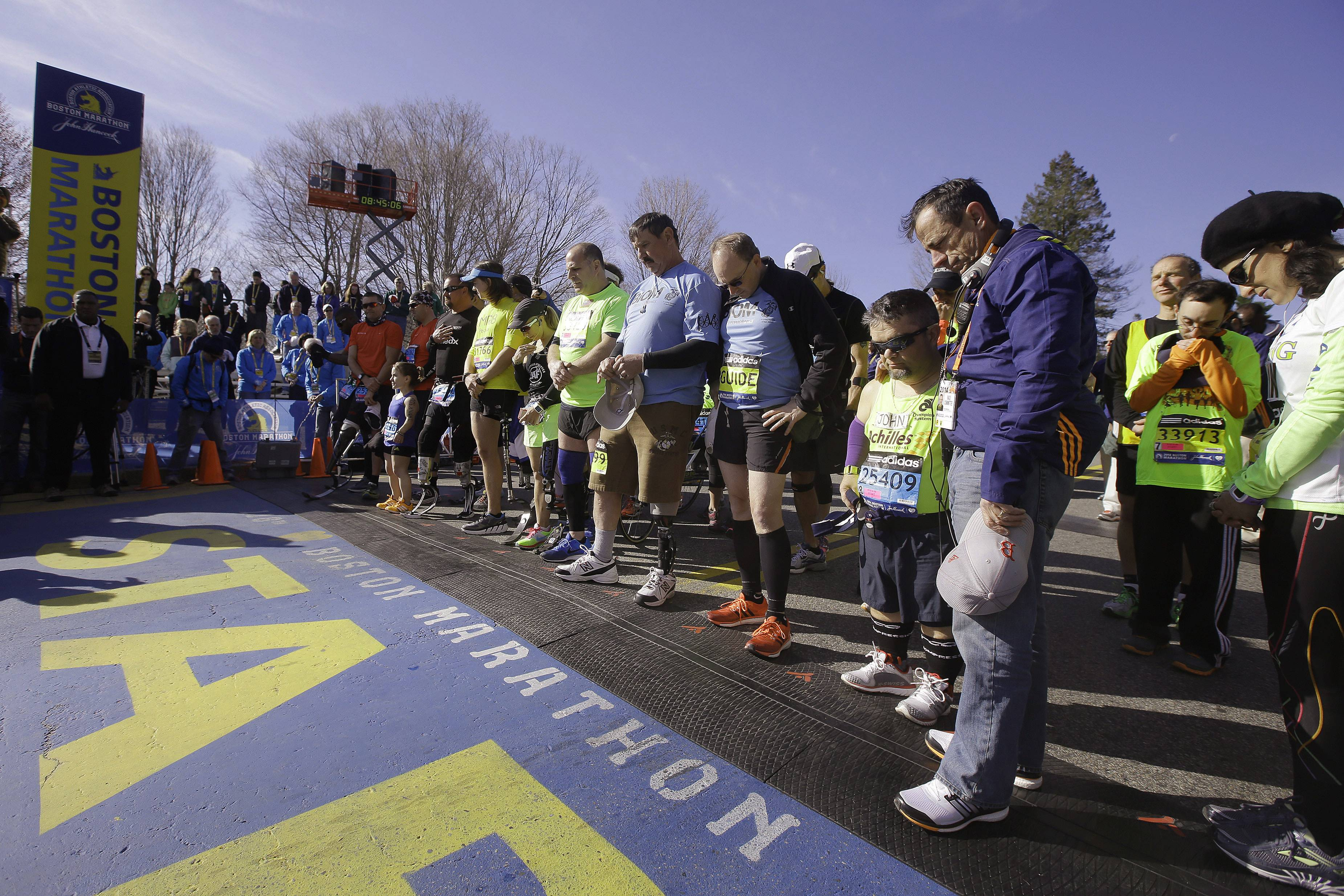 Mobility-impaired runners gather at the start line for a moment of silence before the 118th Boston Marathon Monday, April 21, 2014 in Hopkinton, Mass.