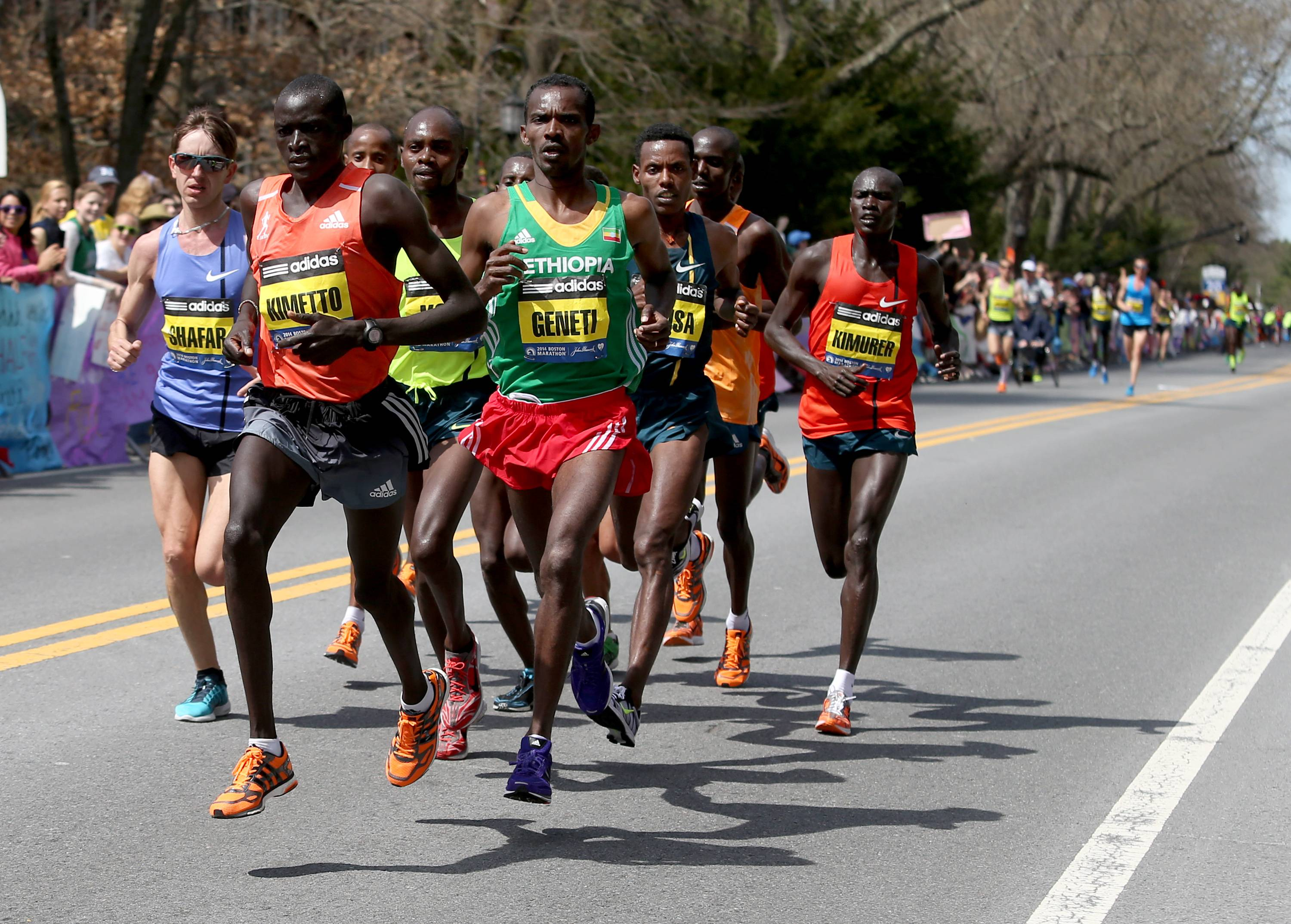 Elite runners lead by Dennis Kimetto, of Kenya, and Markos Geneti, of the United States, pass Wellesley College during the 118th Boston Marathon Monday, April 21, 2014 in Wellesley.