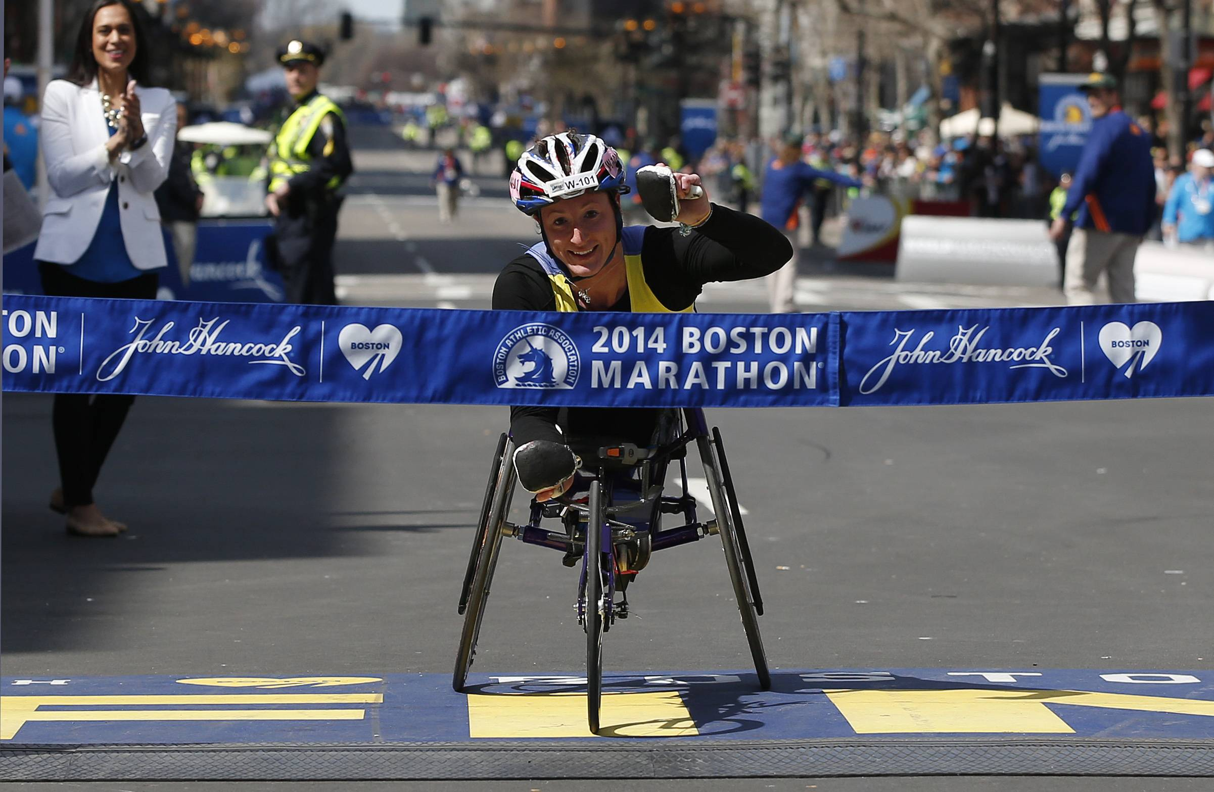 Tatyana McFadden, of the United States, gestures before breaking the tape to win the women's wheelchair division of the 118th Boston Marathon Monday, April 21, 2014 in Boston.