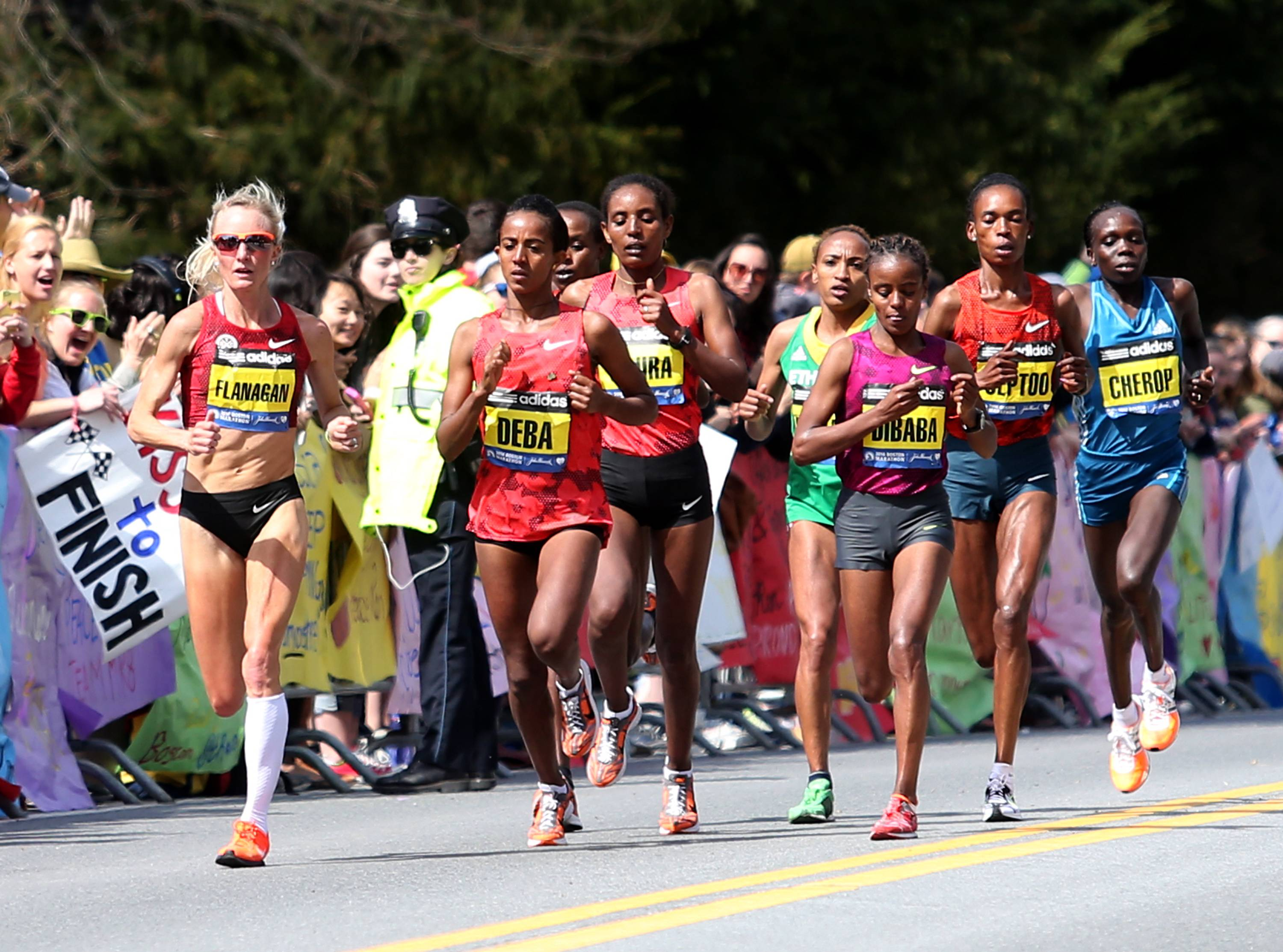 Shalane Flanagan leads the elite pack past Wellesley College during the 118th Boston Marathon Monday, April 21, 2014 in Wellesley.