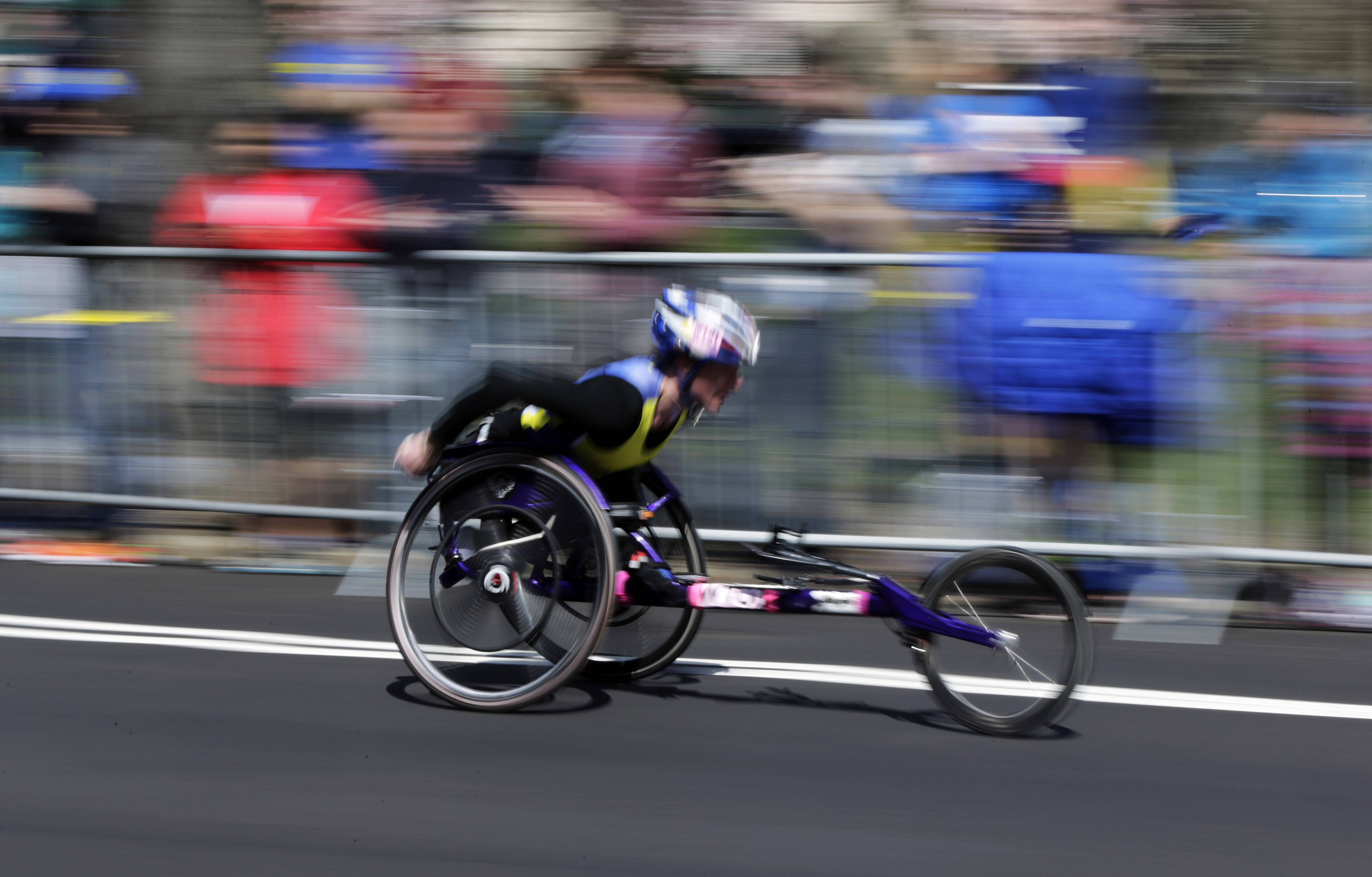 A competitor streaks along the course in the wheelchair division of the 118th Boston Marathon Monday, April 21, 2014 in Boston.