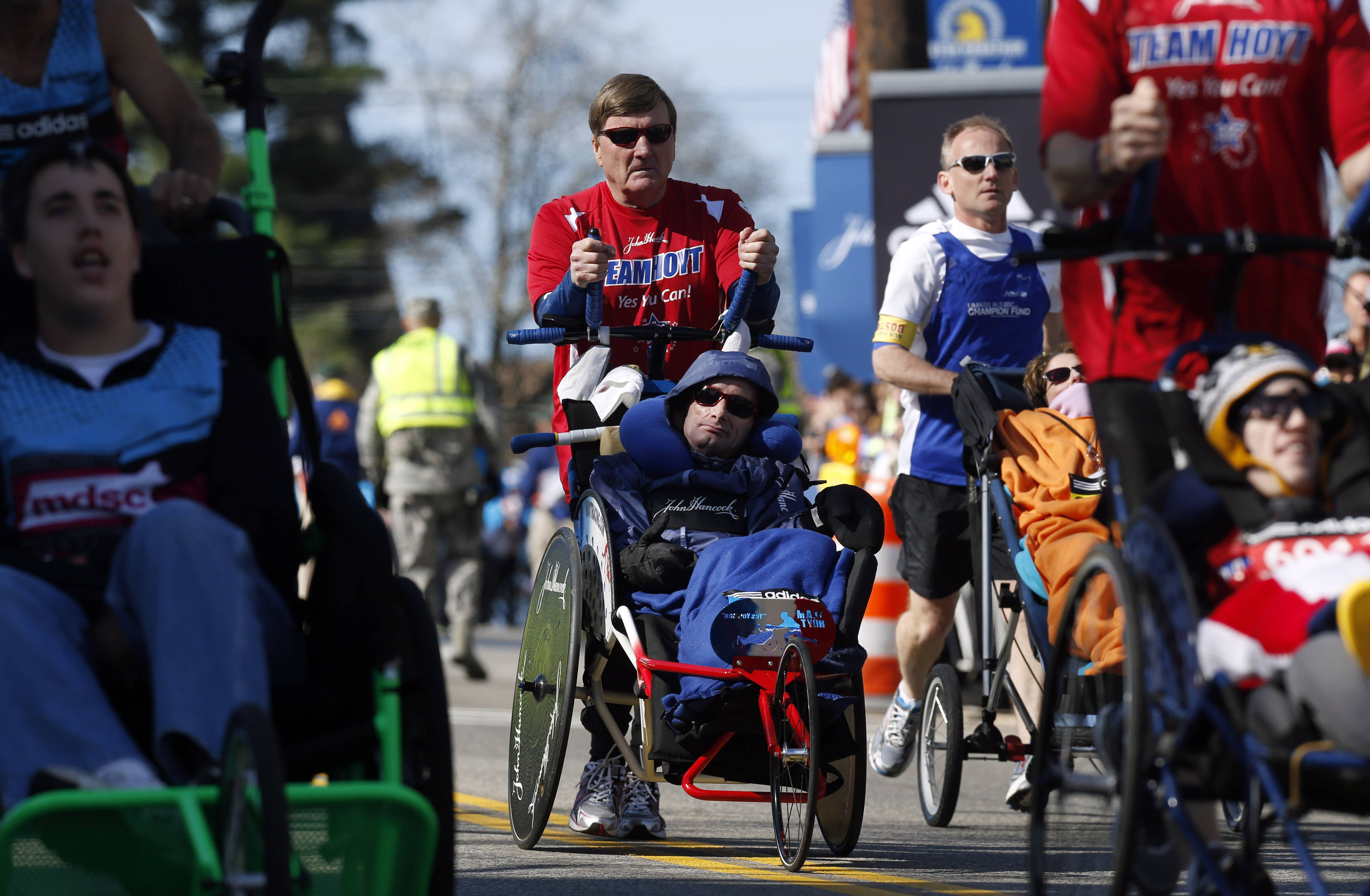 Dick Hoyt pushes his son Rick Hoyt, both from Holland, Mass., center, as they compete in the wheelchair division of the 118th Boston Marathon Monday, April 21, 2014 in Hopkinton, Mass. They are competing in their 32nd Boston Marathon and have said this will be their last.