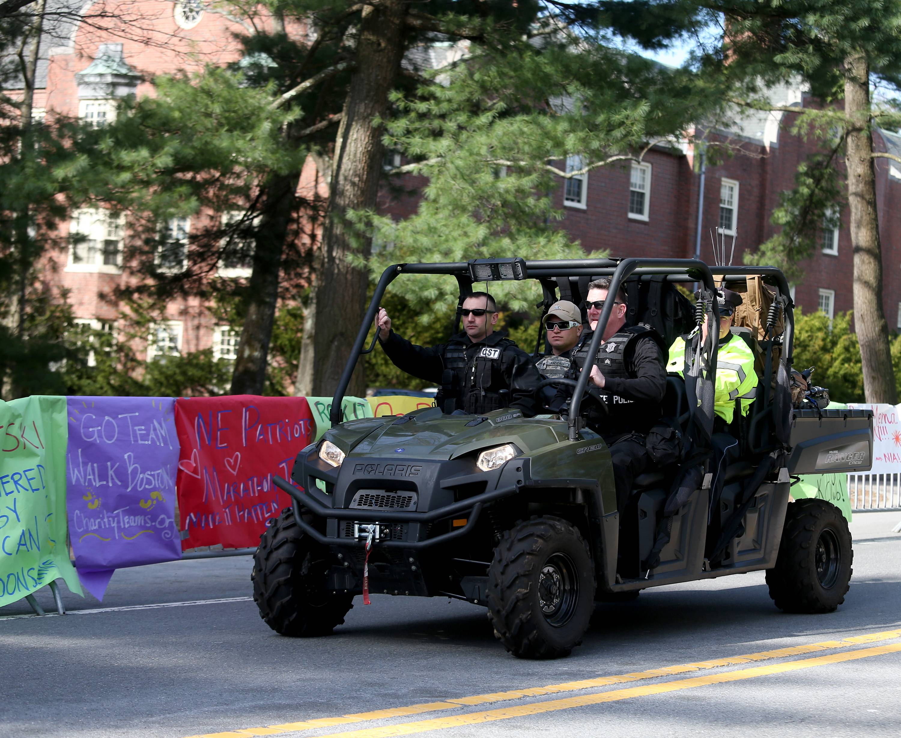 A State Police Special Response team patrols past posters of encouragement at Wellesley College before the start of the 118th Boston Marathon Monday, April 21, 2014 in Wellesley, Mass.