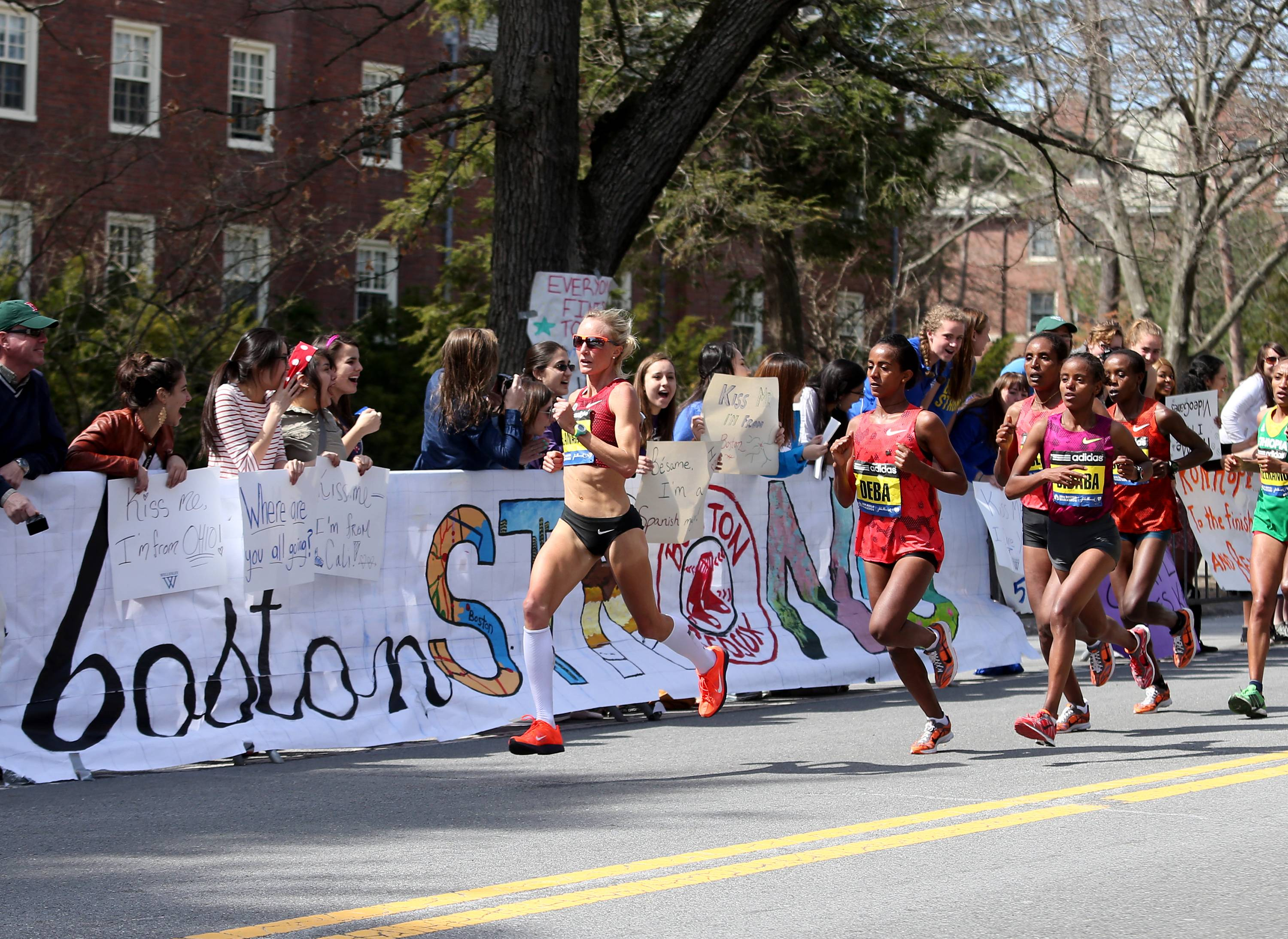 Shalane Flanagan leads Buzunesh Deba, of Ethiopia, and Mare Dibaba, of Ethiopia pass Wellesley College during the 118th Boston Marathon Monday,