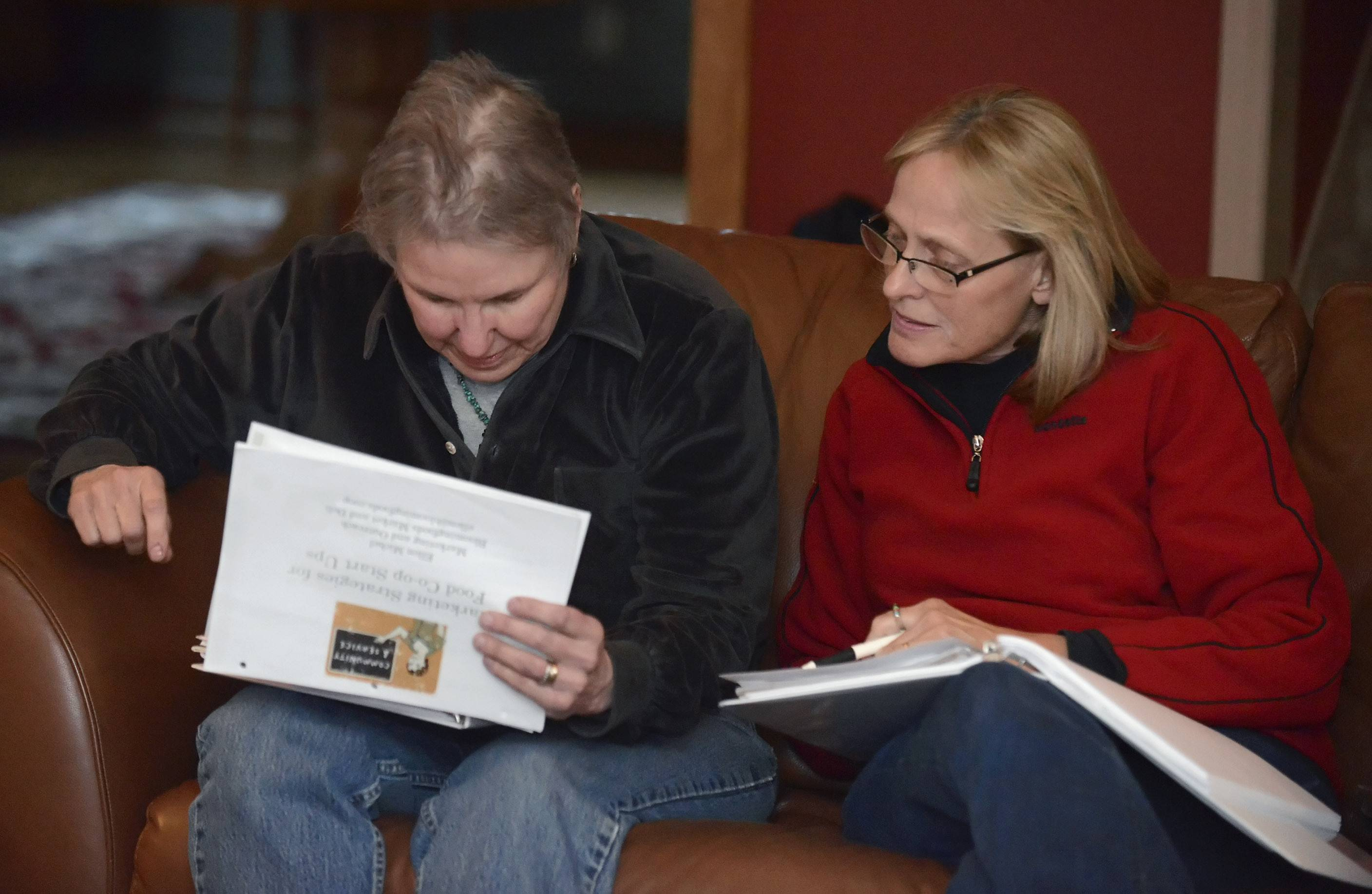 Caron Wenzel of Woodstock, left, and Kim Brix of Marengo review a marketing strategy workbook during a meeting for the yet-to-be-named McHenry area food co-op.