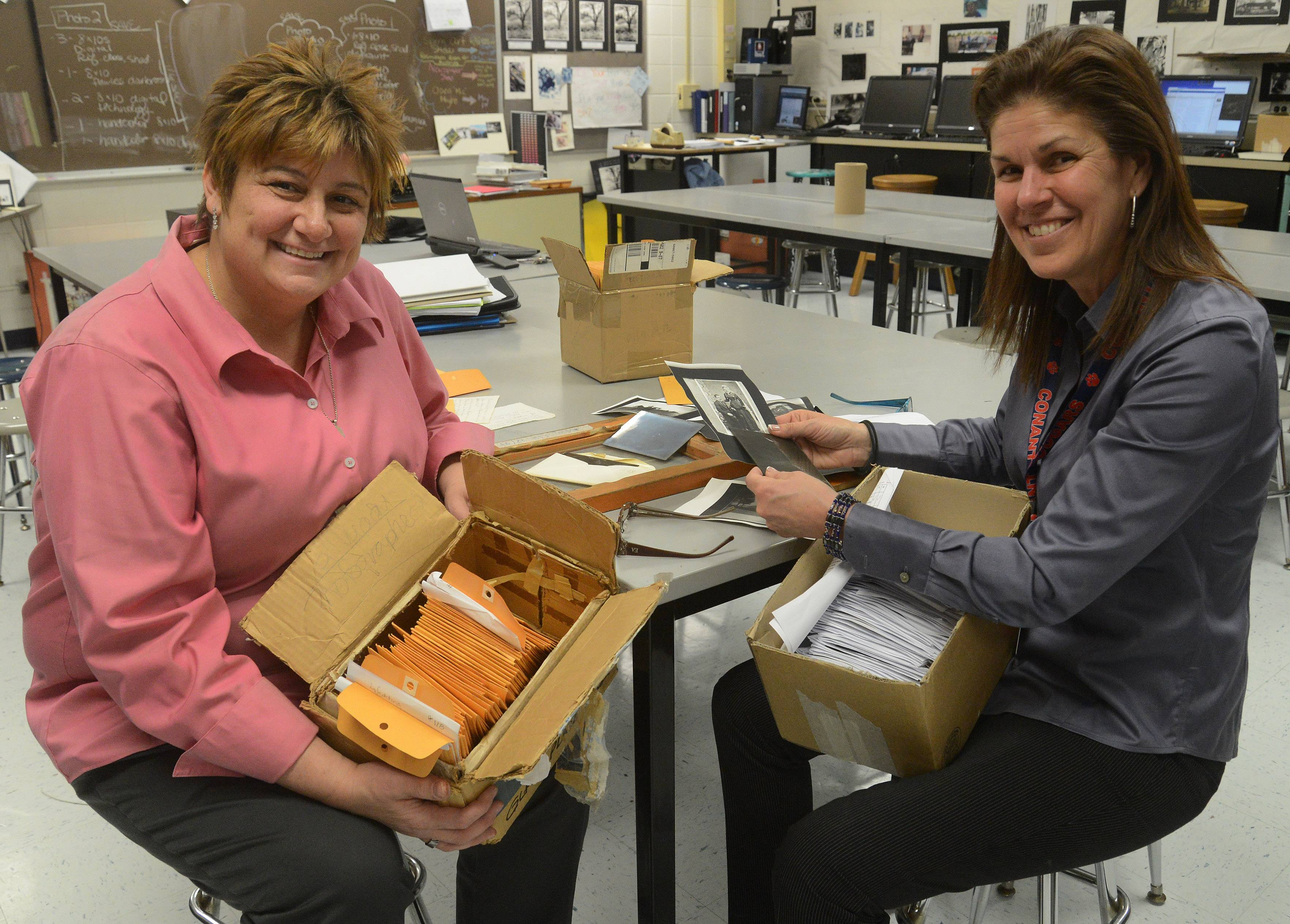 Conant High School teachers Denise Mitchell, left, and Linda Patino-Goergen, with some of the more than 100 glass plate images.