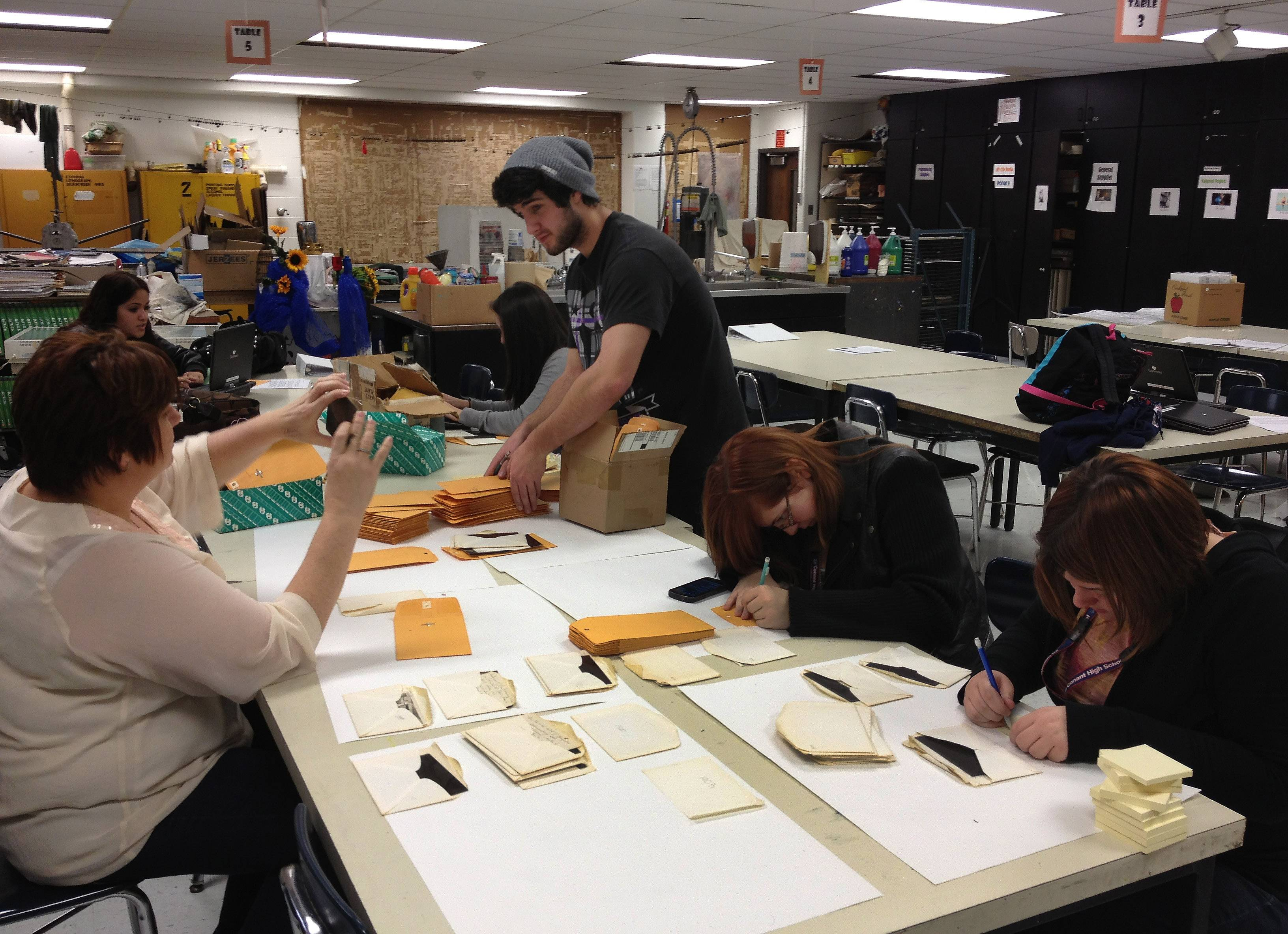 Conant students work on archiving some of the 100-plus glass-plate images they obtained depicting life in Schaumburg more than a century ago. The images will go on display today at the high school.