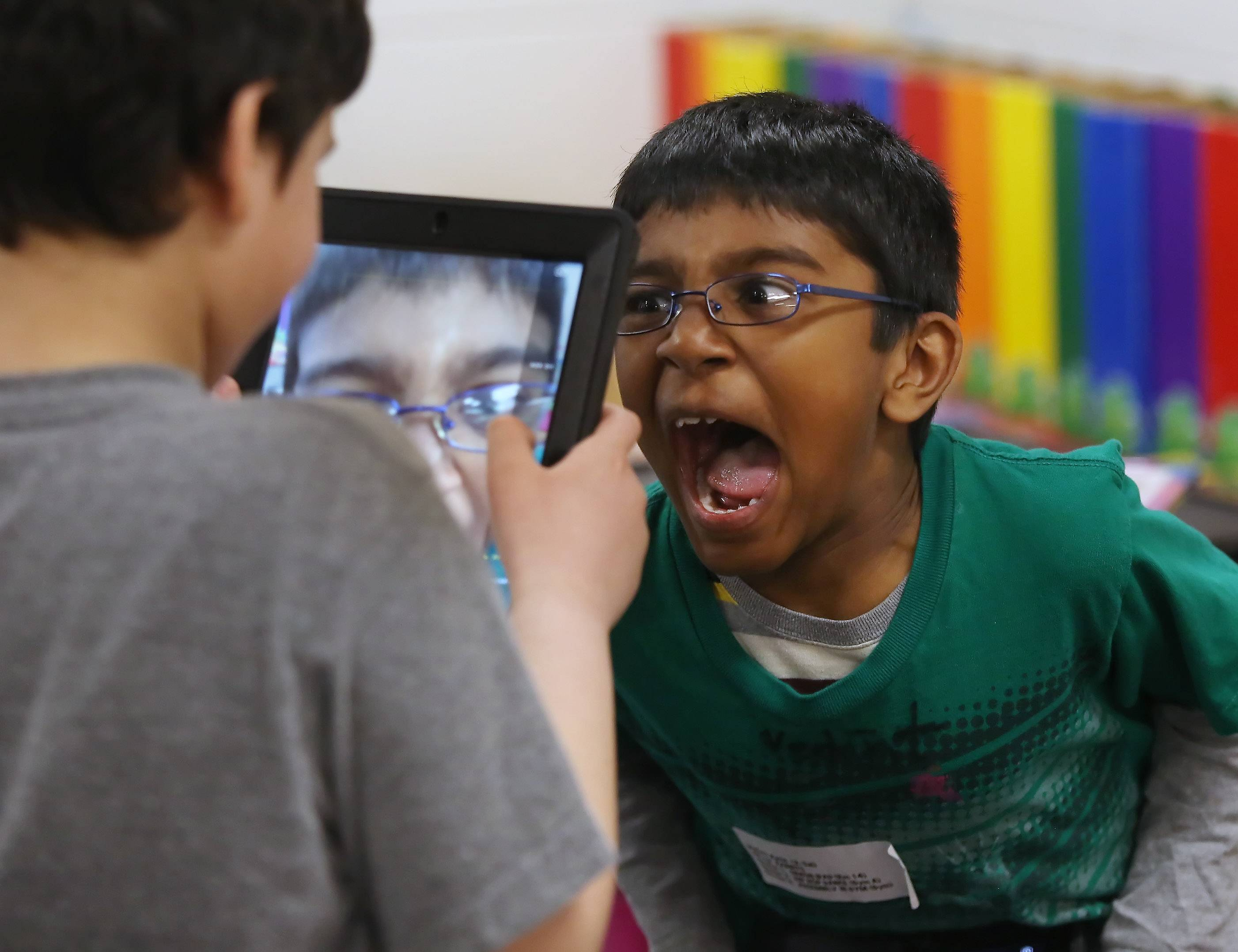 Second grader Vedant Rathi makes a face as Nicholas Rayyan takes his picture with an iPad during Explore the Arts day at Laura B. Sprague School in Lincolnshire on Thursday. The students then took the picture and changed it into a Picasso-style artwork using a special art app.