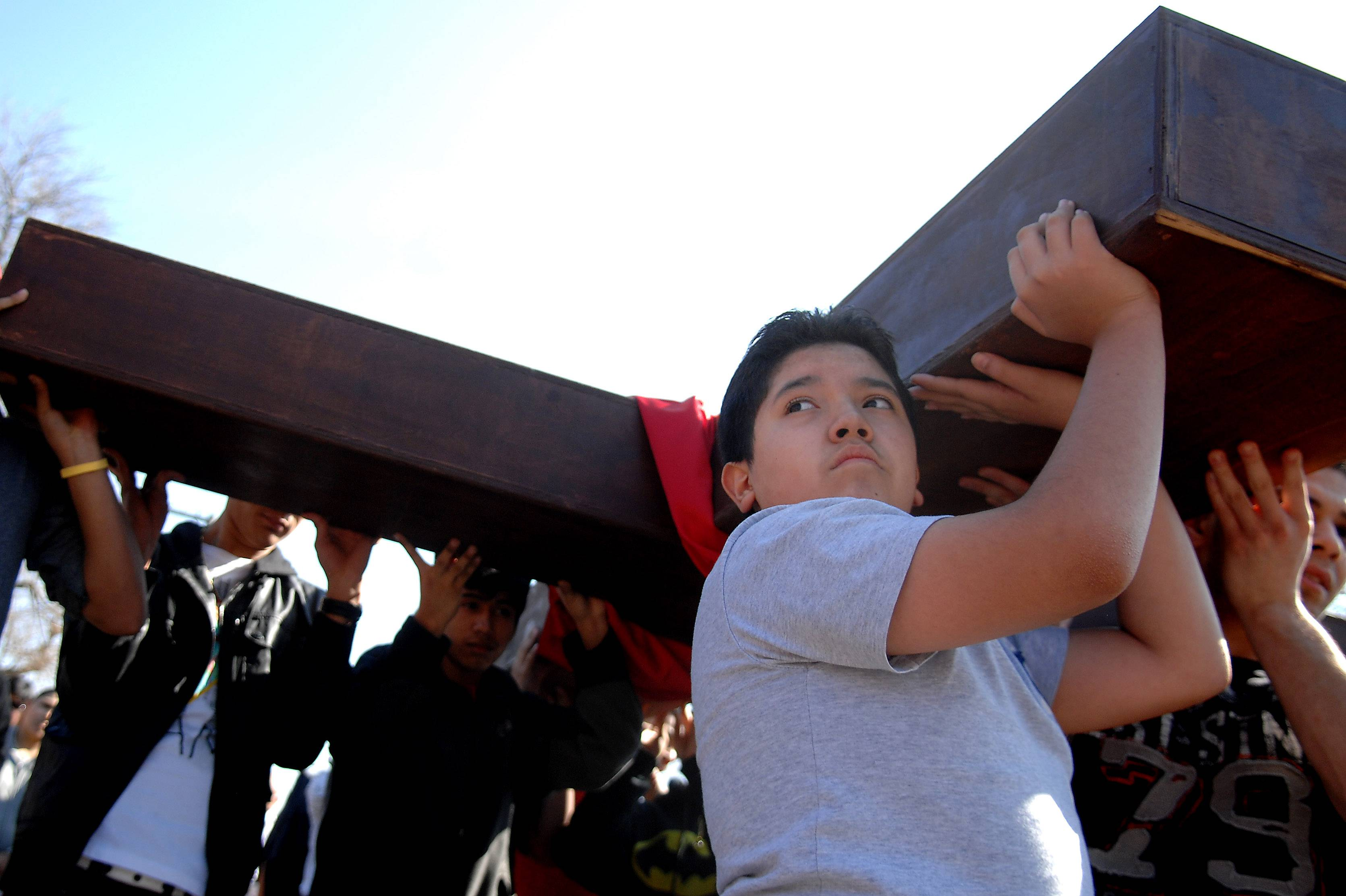 Eliseo Coron, 12, of Elgin, gets a turn carrying the cross during St. Joseph Catholic Church's annual Good Friday Stations of the Cross procession in Elgin.