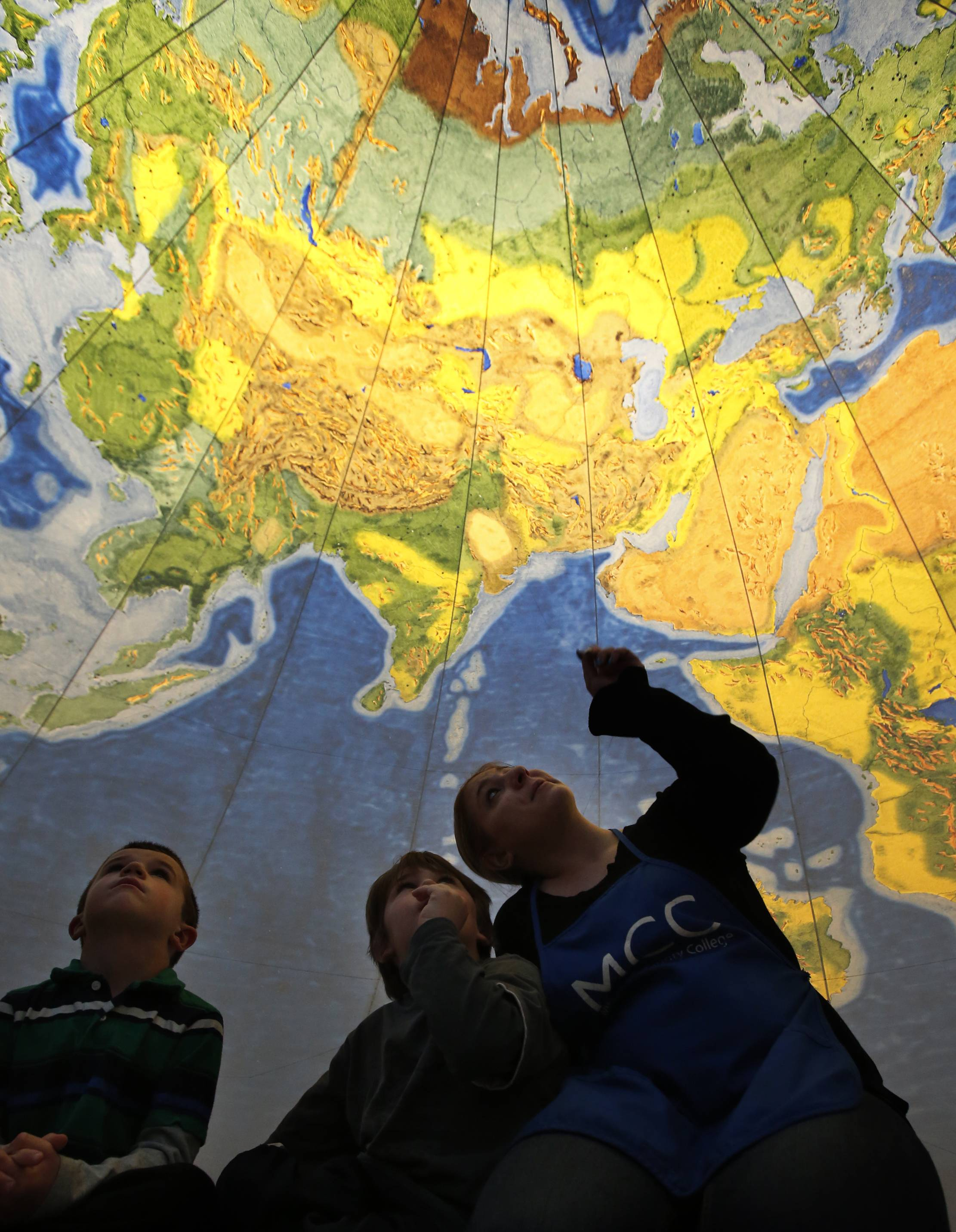 McHenry County College Children's Learning Center students Joshua Dalton, left, and Jaxton Michaels, gaze up from the inside of the inflatable Geosphere Monday on the Crystal Lake campus. Pointing out some of the Earth's features to Jaxton is student teacher Jill Shadwell. Joshua and Jaxton, both 4, are from Crystal Lake. Director Steve Jansen, of The Geographic Society of Chicago, taught the kids about how much water covers the earth versus land, the rainforests, and the relative size of mountains compared with the depths of the oceans.