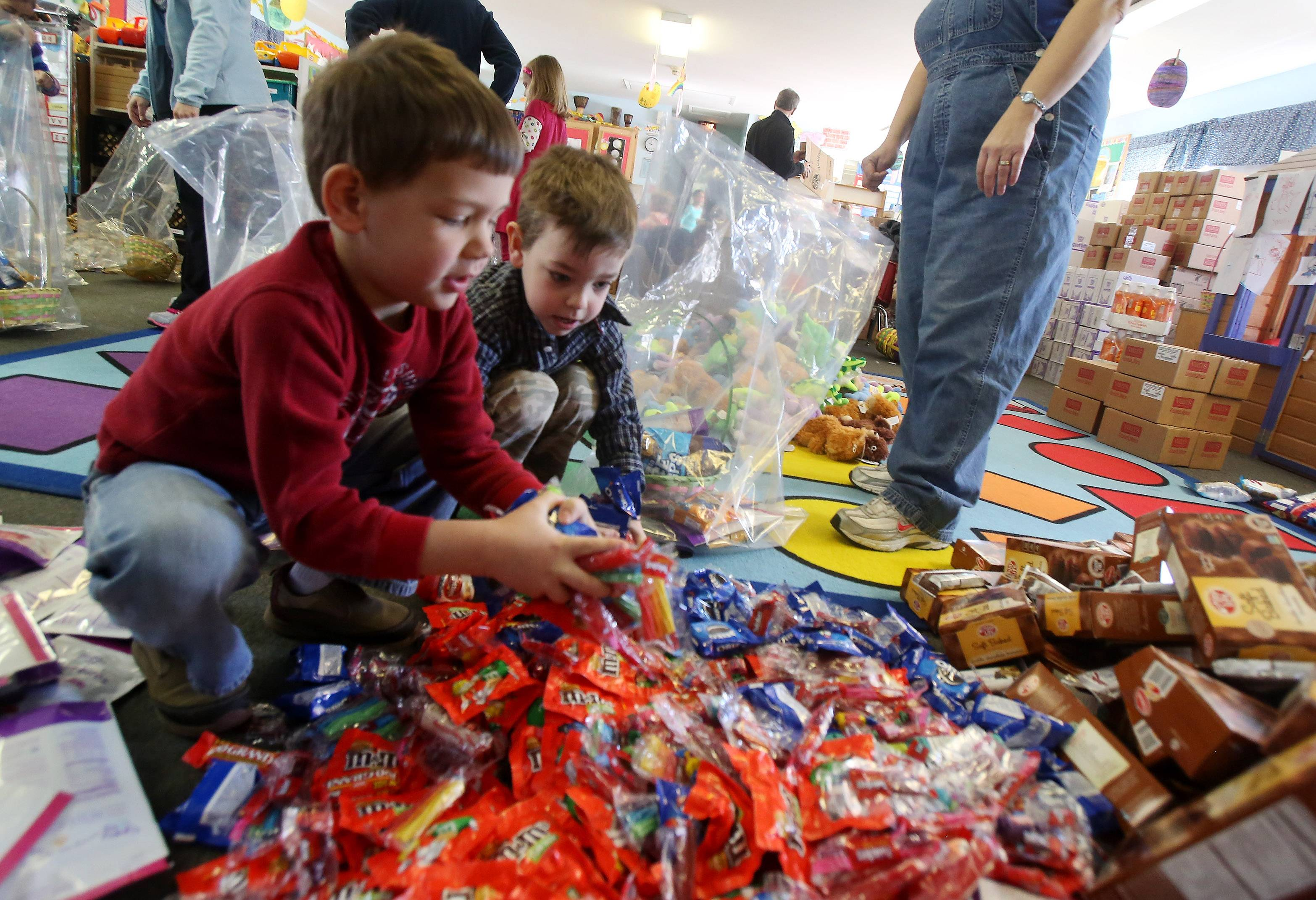 Kindergartners Sebastien Frason, left, and Matthew Bergst, make spring baskets Tuesday at the Lindenhurst Early Childhood Center. Five hundred baskets will be distributed to children through DCFS, Lake County Housing Authority, food pantries, Little City, One Hope United, PADS and other groups.