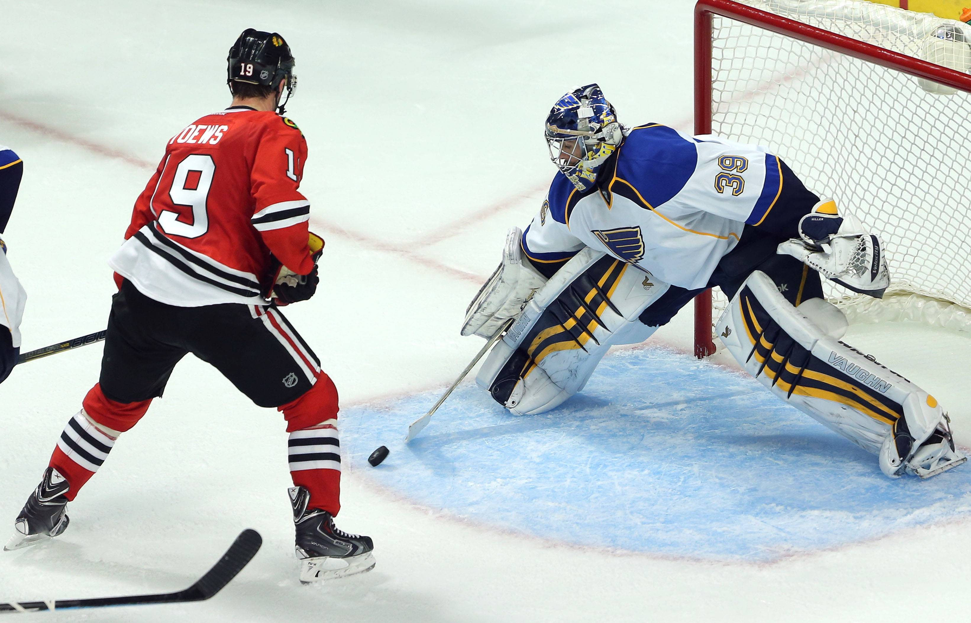 Blackhawks center Jonathan Toews drives on St. Louis Blues goalie Ryan Miller during game 3 of the NHL first-round Stanley Cup playoffs Monday night in Chicago.
