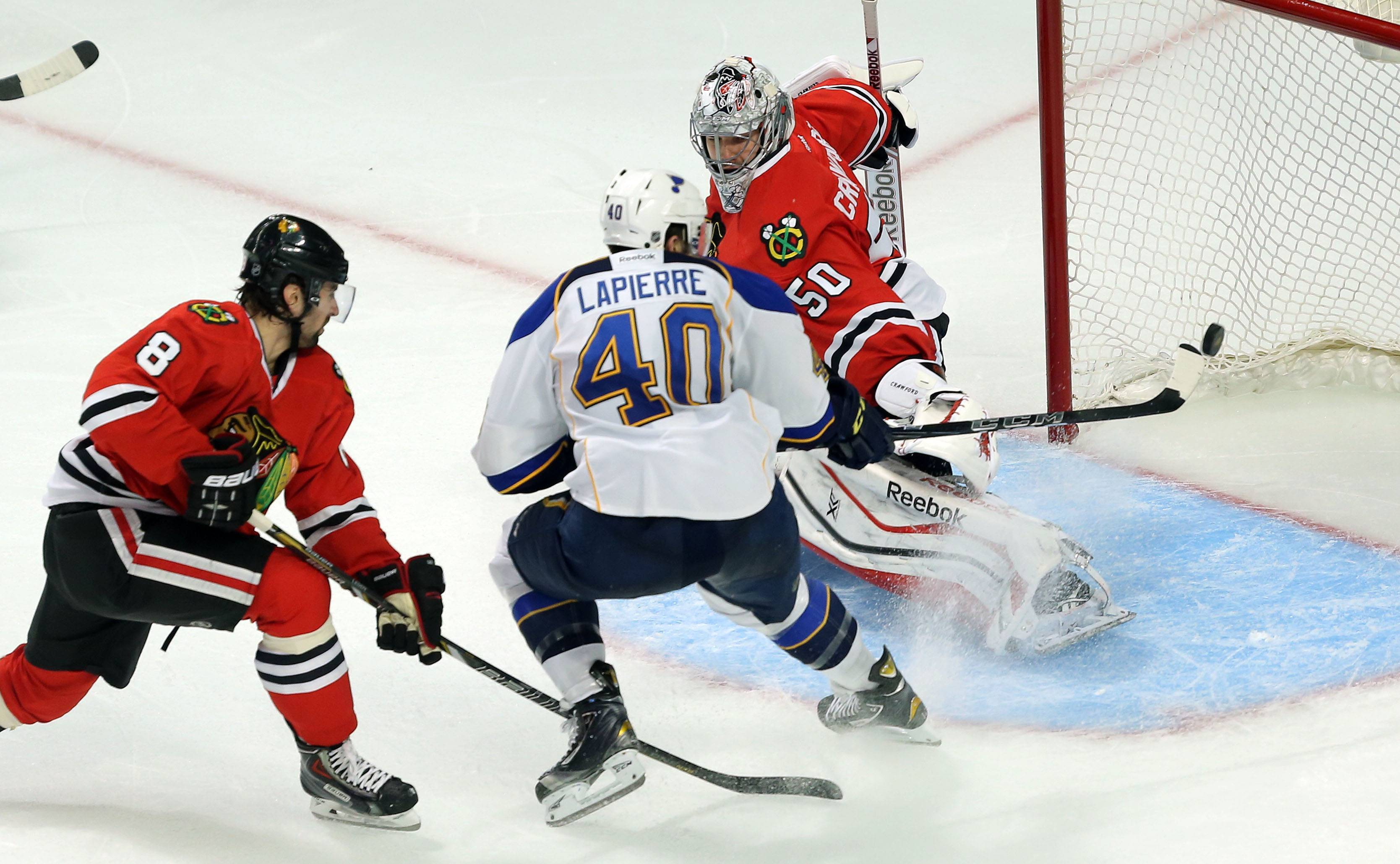 St. Louis Blues center Maxim Lapierre drives on Chicago Blackhawks goalie Corey Crawford.