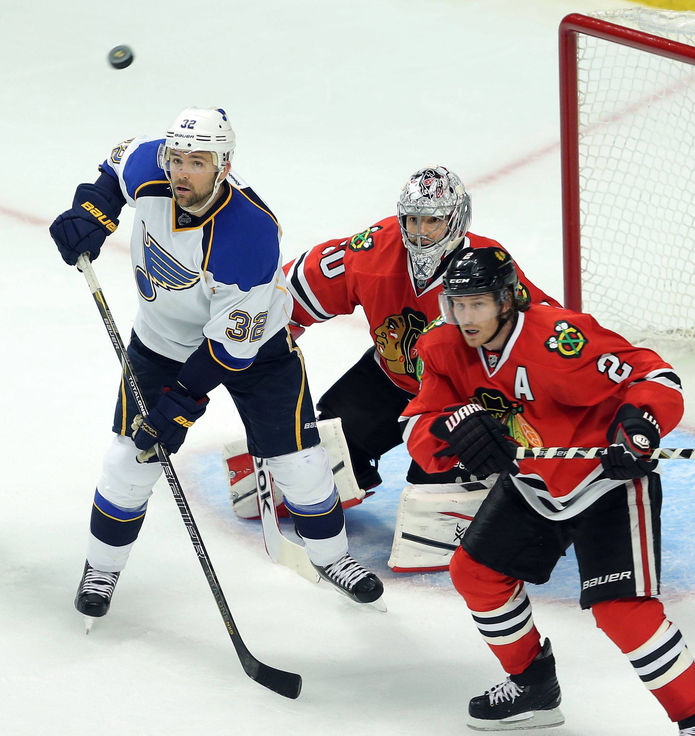 St. Louis Blues left wing Chris Porter, Chicago Blackhawks goalie Corey Crawford  and Chicago Blackhawks defenseman Duncan Keith watch as a puck flies.