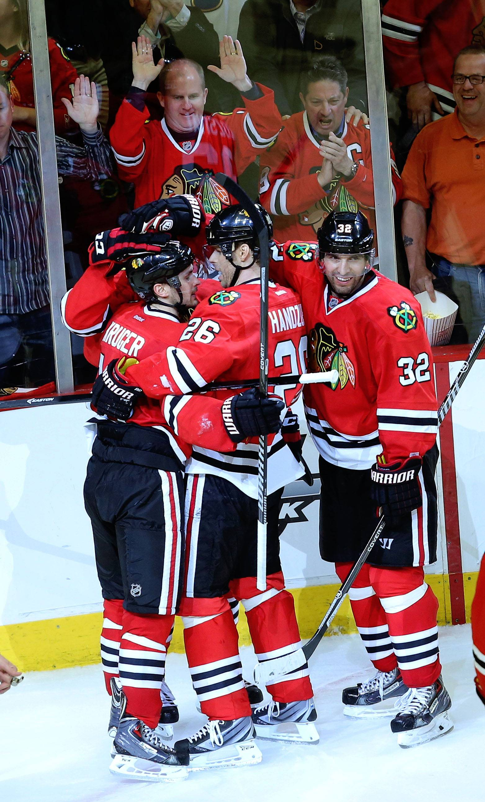 Hawks players hug Chicago Blackhawks center Marcus Kruger after his late goal.