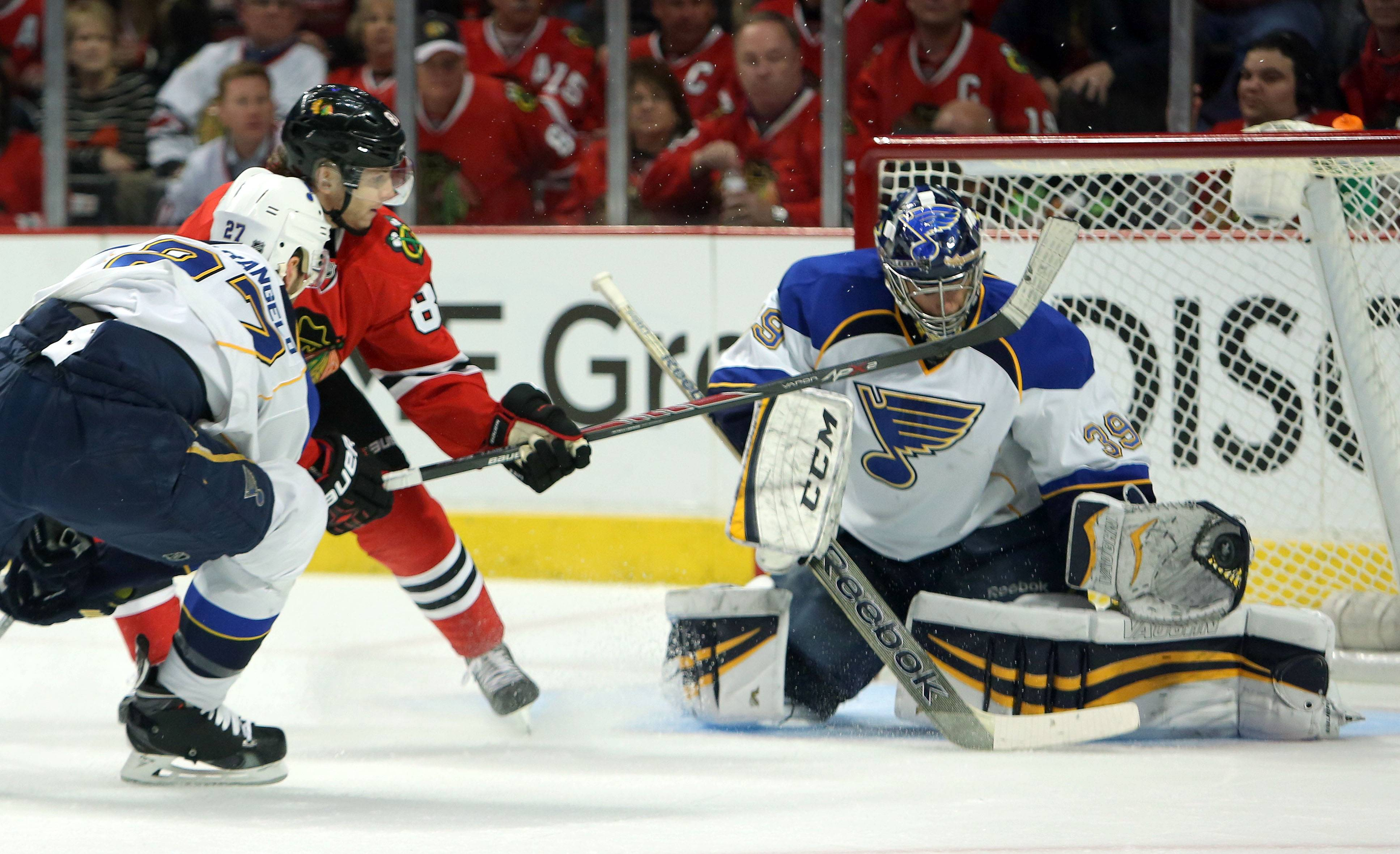 Chicago Blackhawks left wing Patrick Sharp and St. Louis Blues defenseman Roman Polak battle.